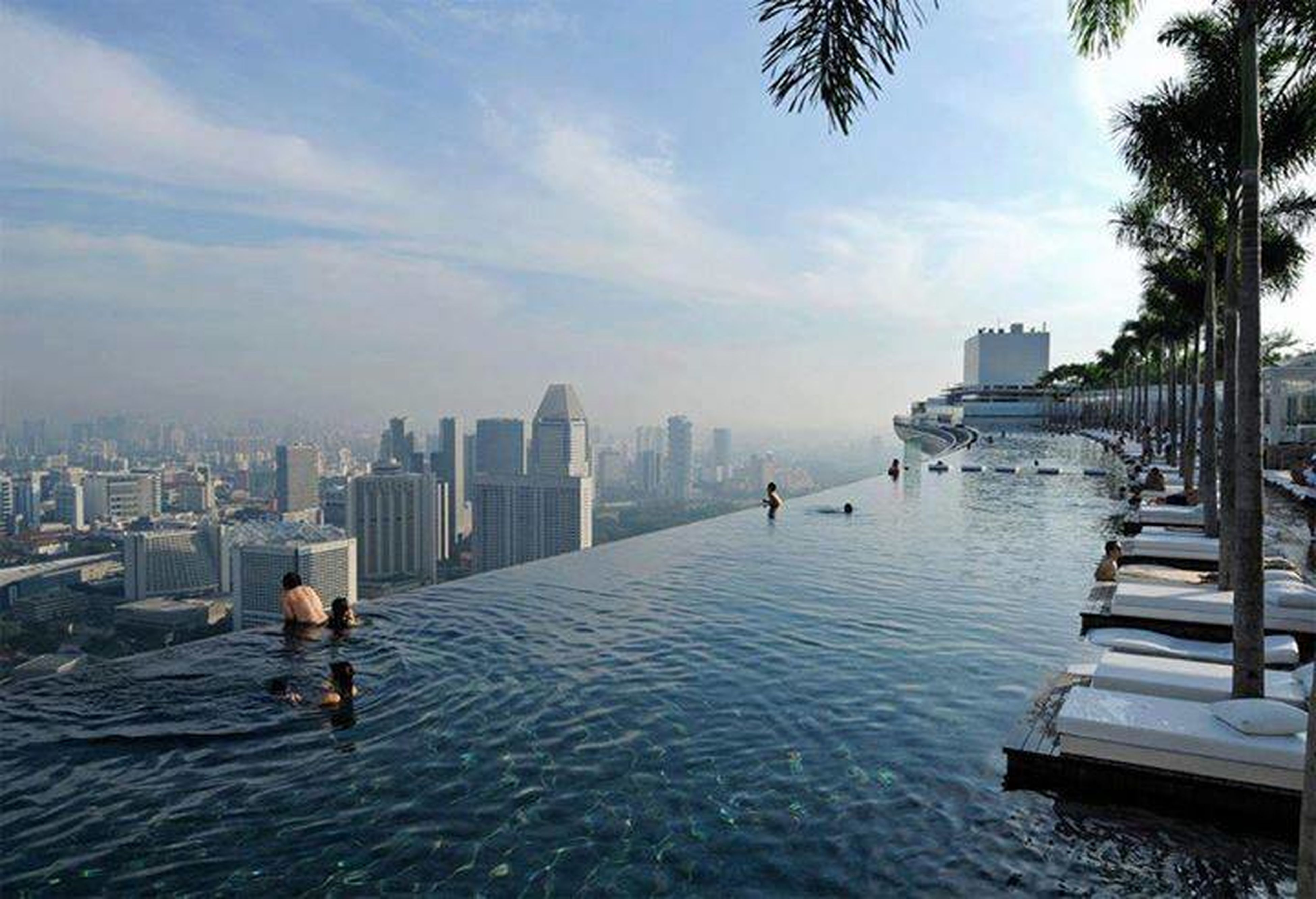 architecture, building exterior, water, built structure, city, lifestyles, leisure activity, waterfront, sky, river, men, city life, cityscape, skyscraper, full length, rear view, person, day