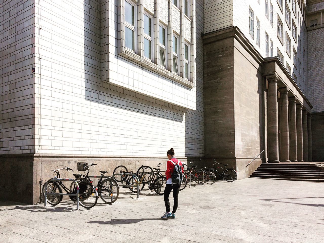 bicycle, transportation, architecture, built structure, building exterior, city life, day, city, sunlight, full length, real people, mode of transport, outdoors, one person, women, men, young adult, adult, adults only, people