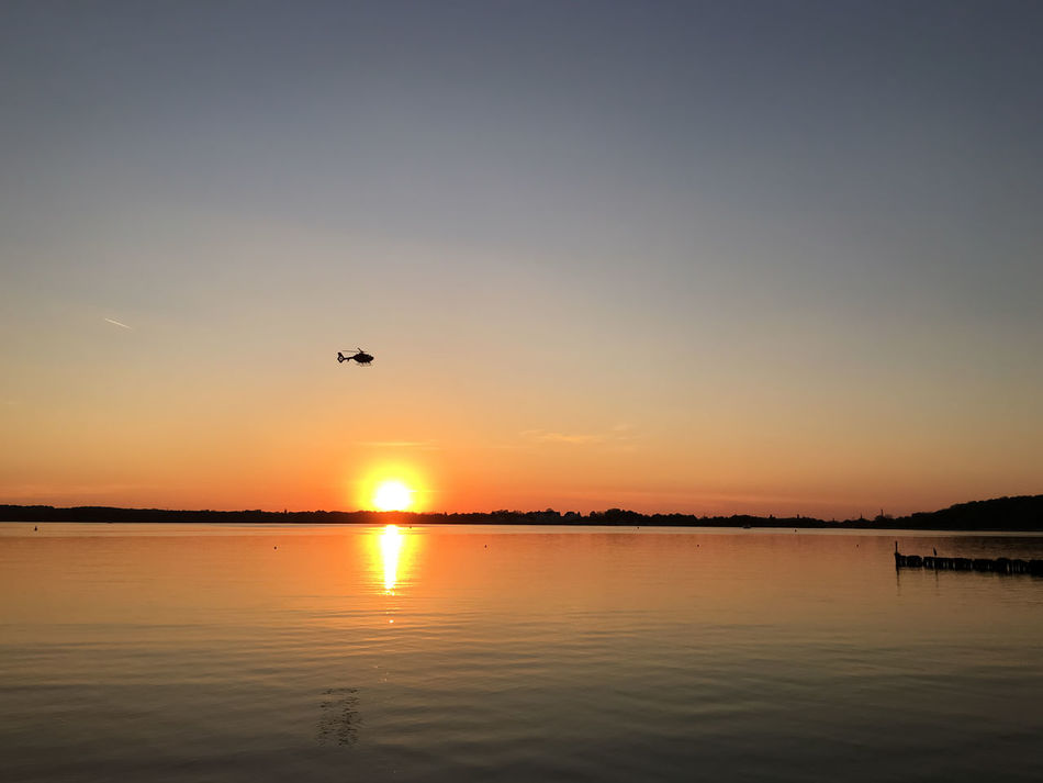 helicopter is flying near the lake at sunset Airlift Beauty In Nature Caputh Eve Evening Helicopter Idyllic Lake Lake View Nature Non-urban Scene Outdoors Reflection Schwielowsee Sky Sun Sundown Sunset Sunshine Water