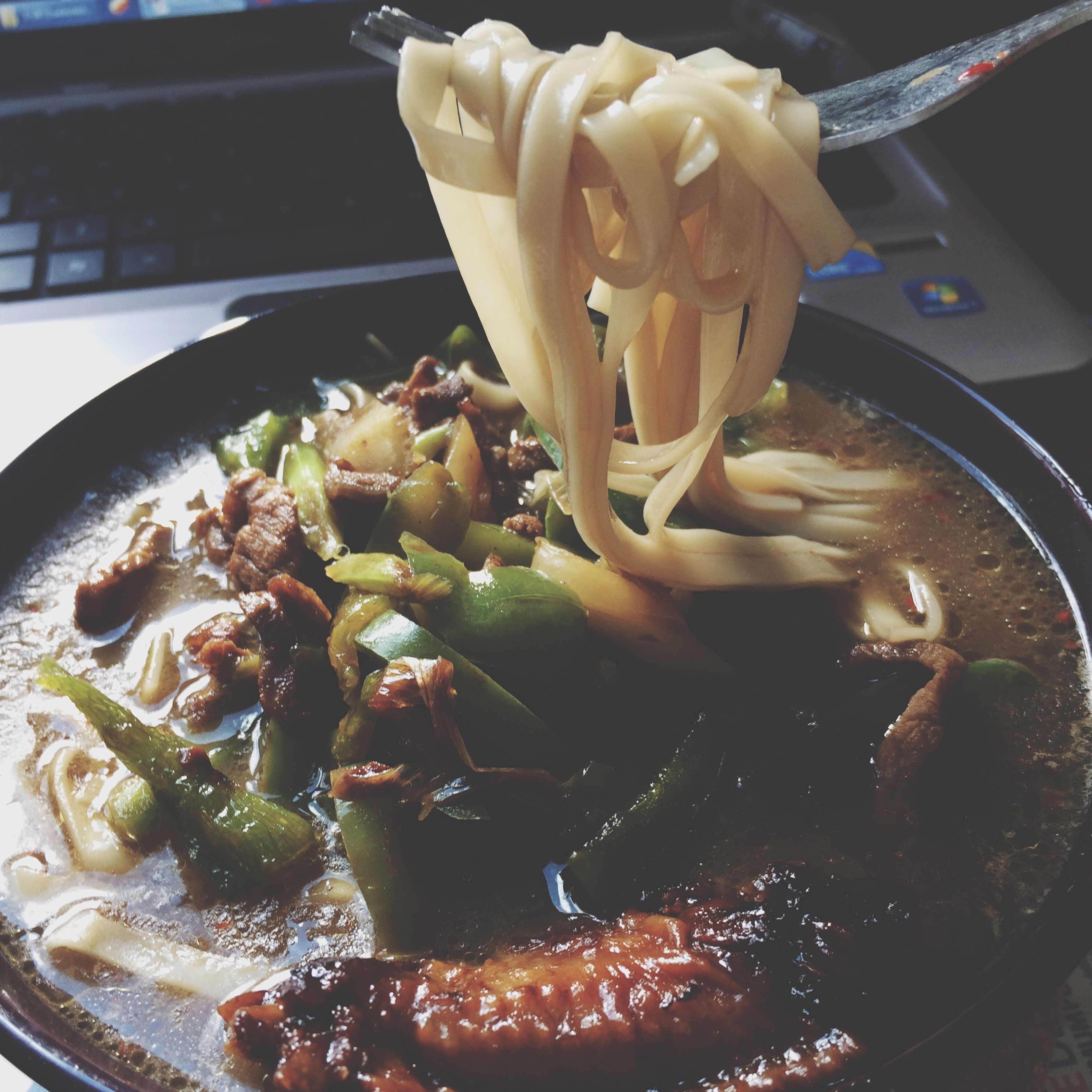 Chinese noodles with a chinken wing and green peppers
