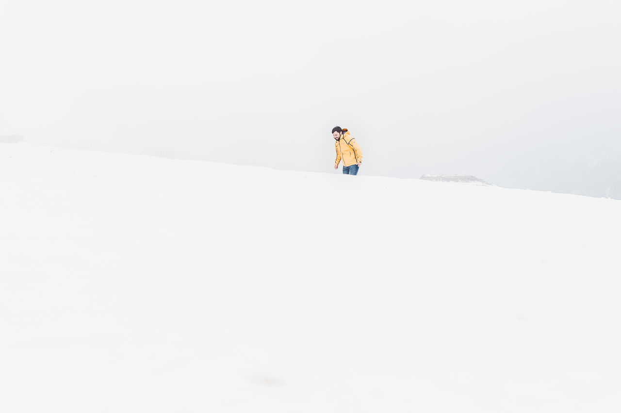 Man Walking On Snow Against Clear Sky