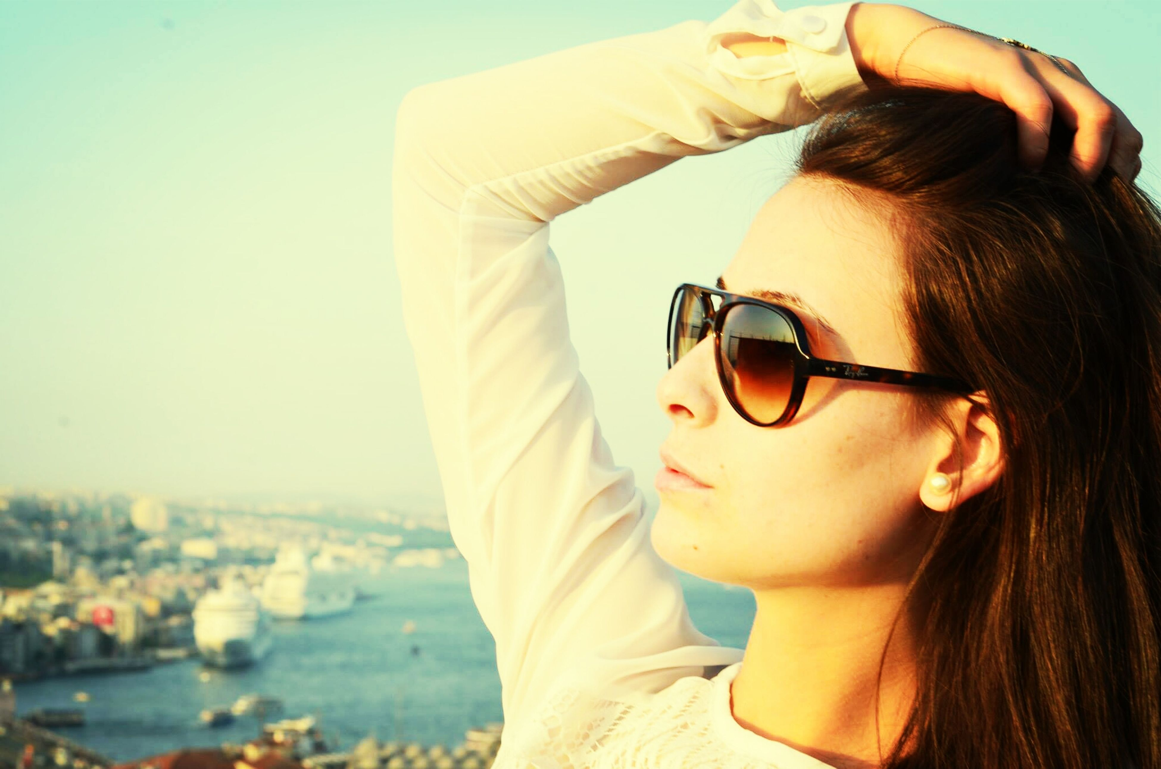 person, headshot, young adult, lifestyles, sunglasses, leisure activity, young women, focus on foreground, head and shoulders, looking at camera, portrait, close-up, human face, front view, smiling, water, holding, casual clothing