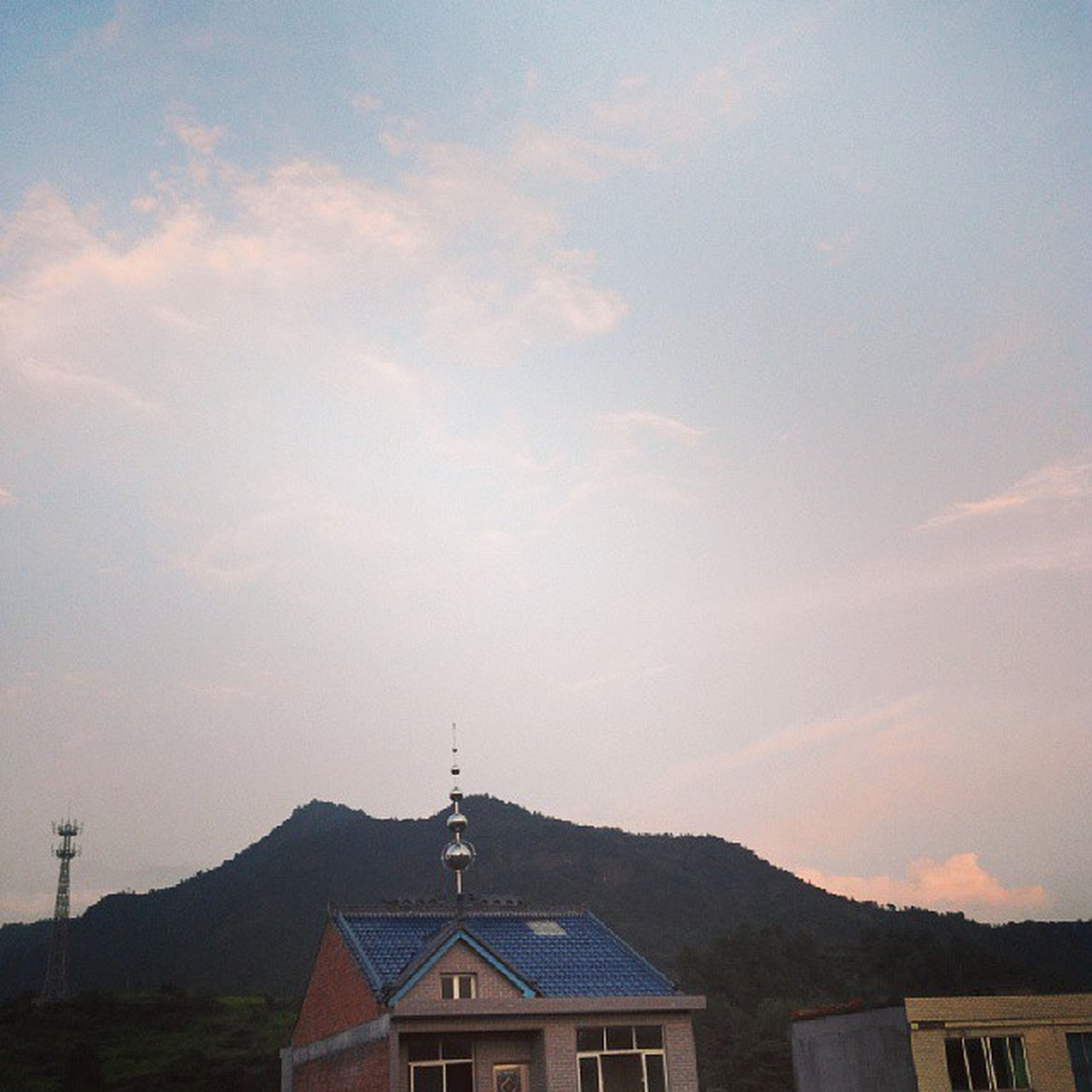 building exterior, architecture, built structure, mountain, sky, house, mountain range, religion, church, spirituality, cloud - sky, roof, place of worship, high section, scenics, beauty in nature, residential structure, low angle view, town