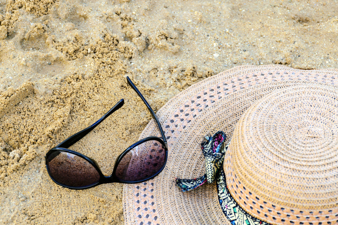High Angle View Of Sun Hat And Sunglasses On Beach