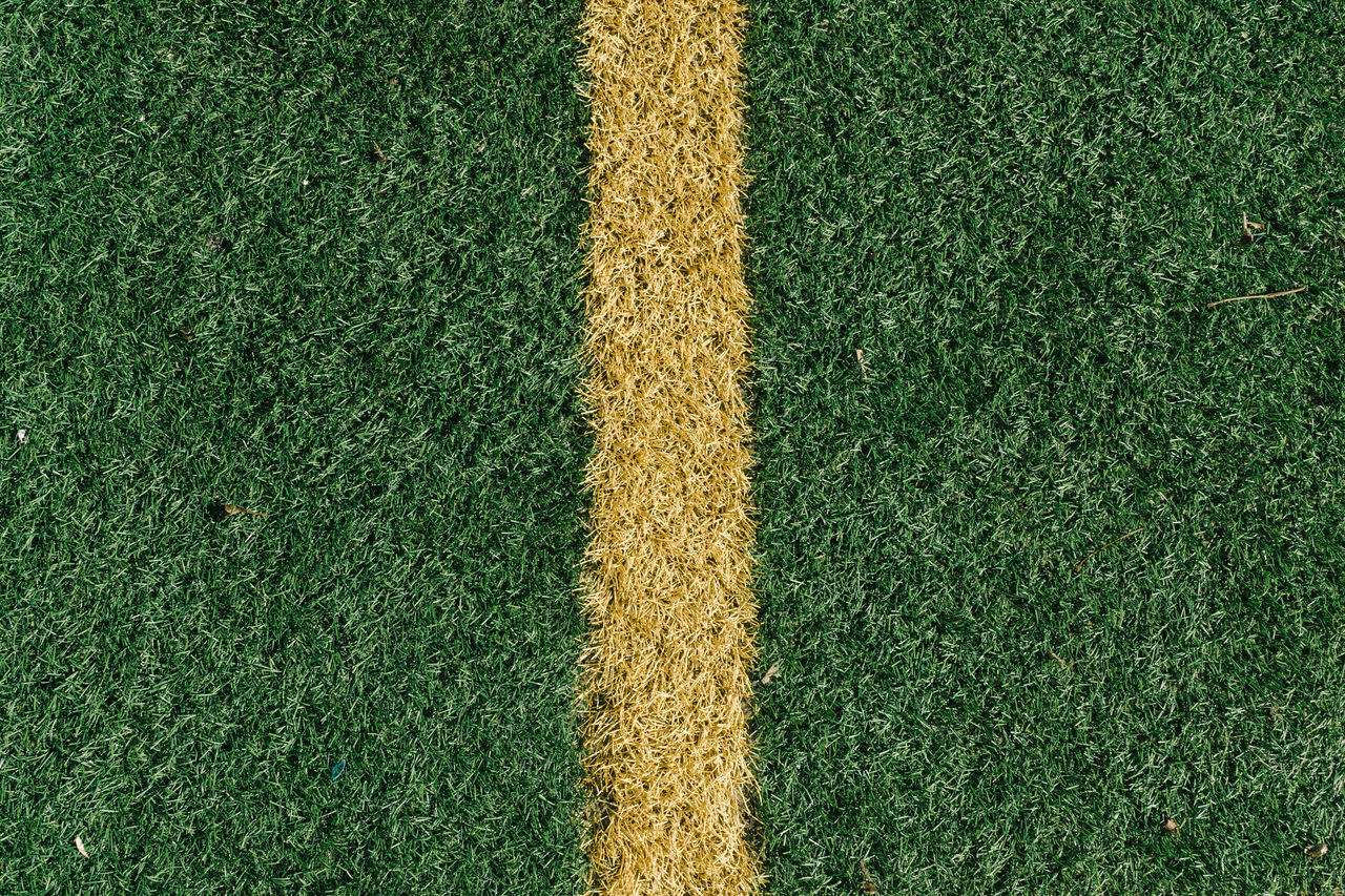 Yellow line on green artificial sports field grass activity artificial background close-up Copy Space day Field Football fresh Grass Green LINE no people outdoors soccer sports texture turf yellow
