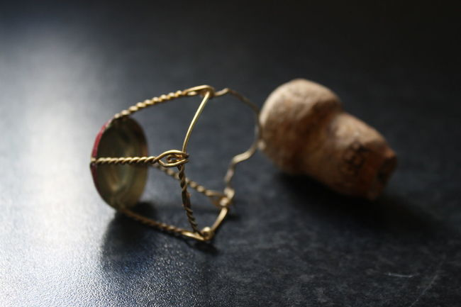 a champagne cork and wire Alcohol Black Color Brown Champagne Close-up Cork Cork And Wire Focus On Foreground Fragility Natural Pattern Nature No People Selective Focus Still Life Two Objects Vignette Wire
