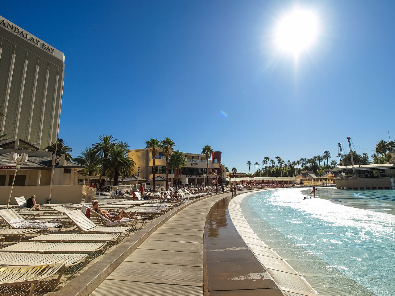 swimming pool, sunlight, palm tree, sun, water, architecture, outdoors, built structure, blue, clear sky, tree, summer, building exterior, day, sky, no people
