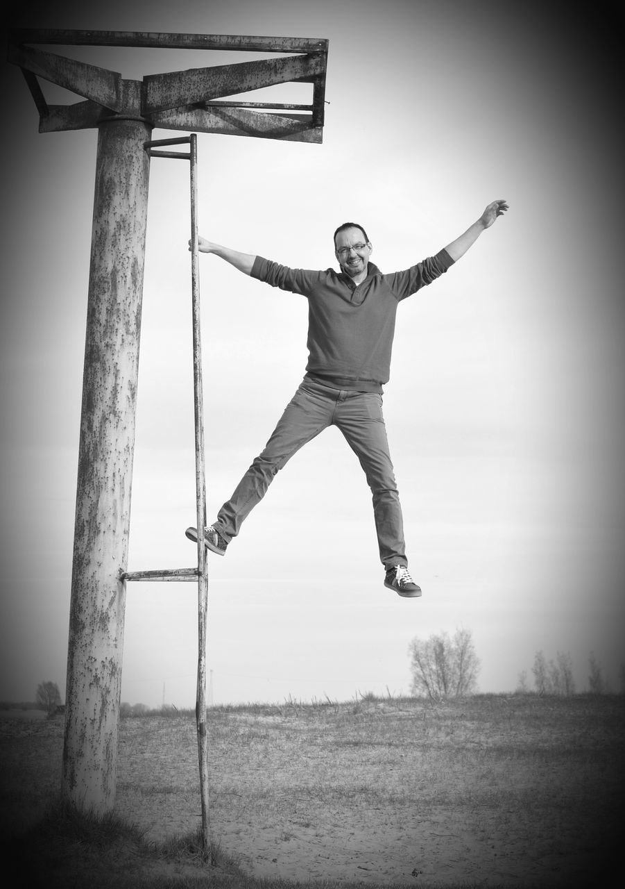 Portrait Of Happy Man With Arms Outstretched Balancing On Pole Against Sky