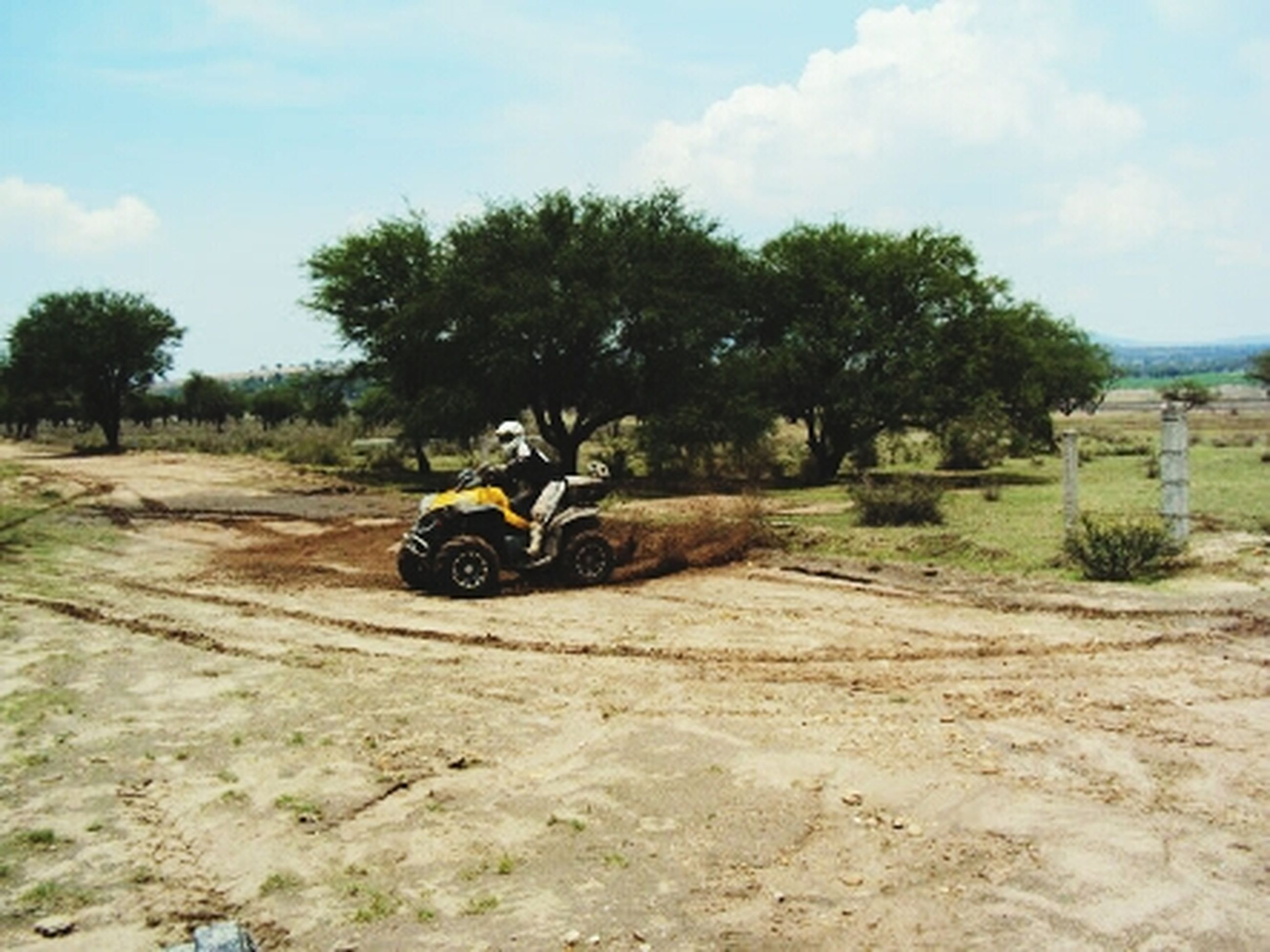 transportation, sky, land vehicle, tree, mode of transport, landscape, cloud - sky, dirt road, bicycle, road, nature, field, full length, day, riding, sand, cloud, tranquility