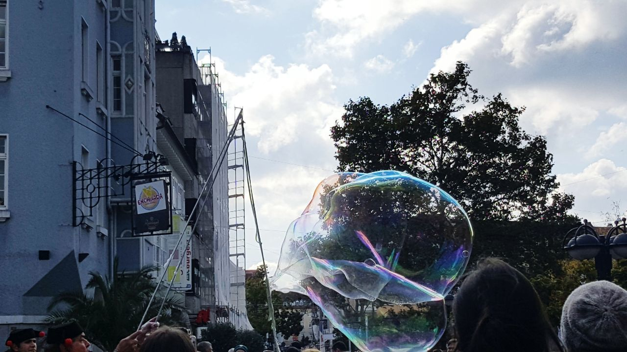 built structure, architecture, bubble, building exterior, real people, bubble wand, sky, day, fragility, men, large group of people, cloud - sky, tree, outdoors, people