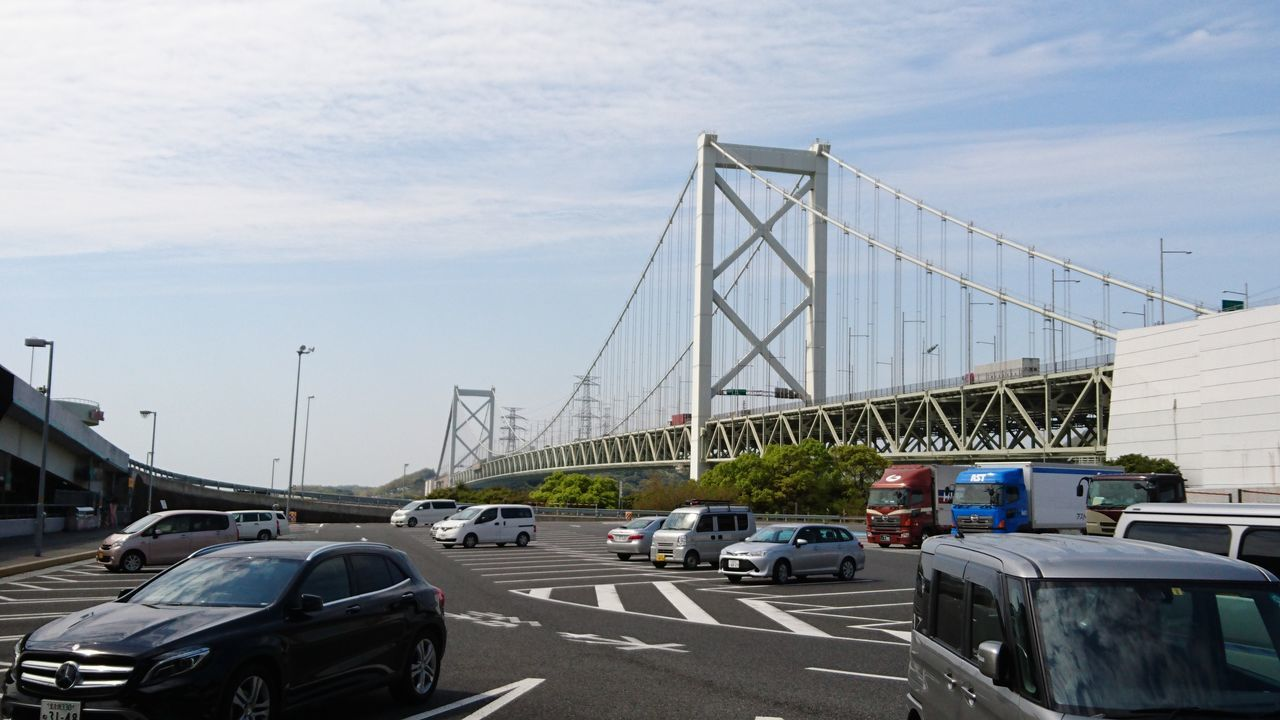 car, transportation, land vehicle, architecture, mode of transport, built structure, bridge - man made structure, road, sky, connection, day, cloud - sky, outdoors, no people, building exterior, city, modern