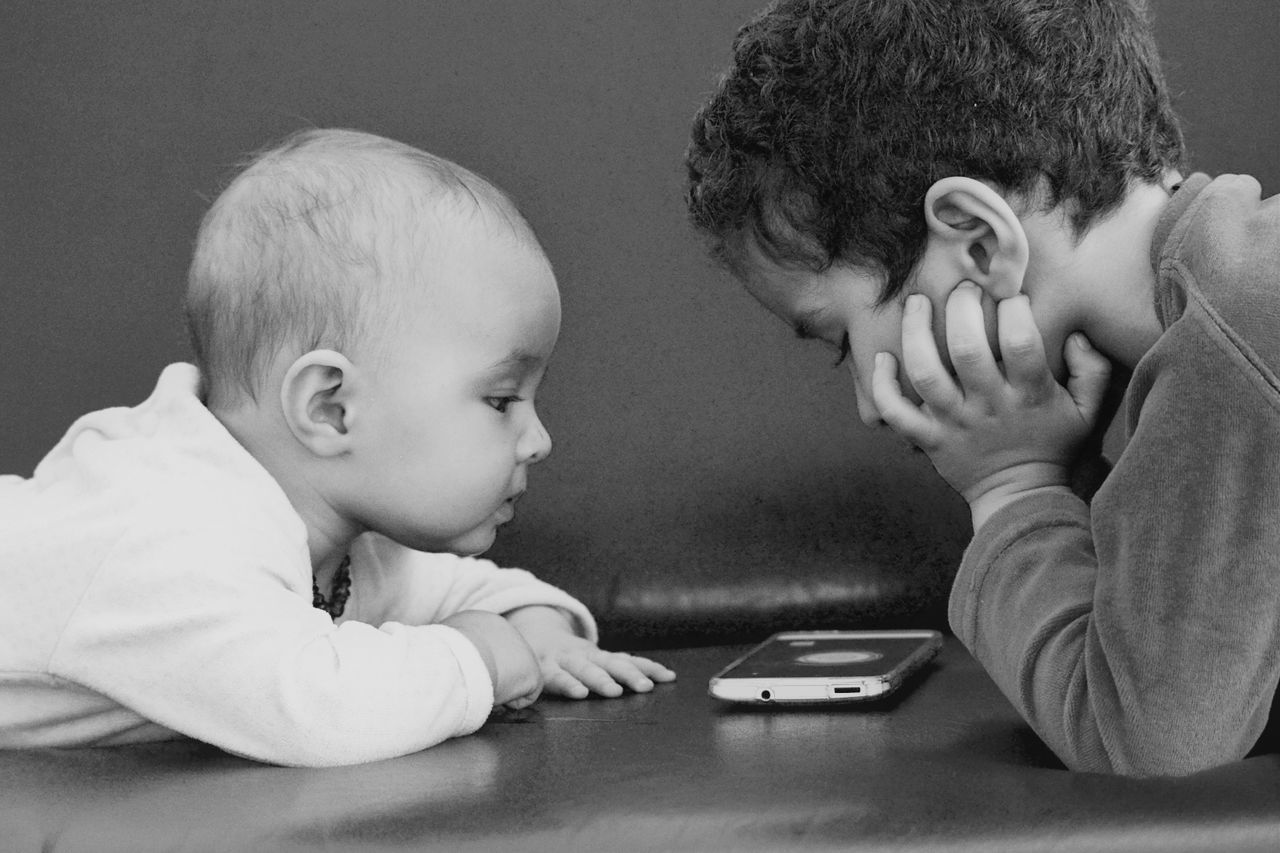 childhood, boys, innocence, indoors, technology, wireless technology, playing, two people, connection, baby, cute, side view, togetherness, toddler, table, real people, communication, bonding, headshot, close-up, friendship, day, people