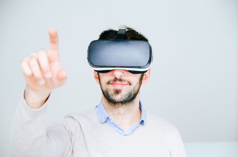 3-d Glasses Adult Adults Only Cyberspace Futuristic Human Body Part Human Hand Indoors  Innovation Interactivity Men One Man Only One Person Only Men People Smiling Studio Shot Technology Virtual Reality Virtual Reality Simulator Vr Wearable Computer Wireless Technology