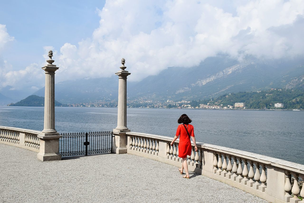 Full Length Rear View Of Woman In Red Dress Walking By River Against Cloudy Sky