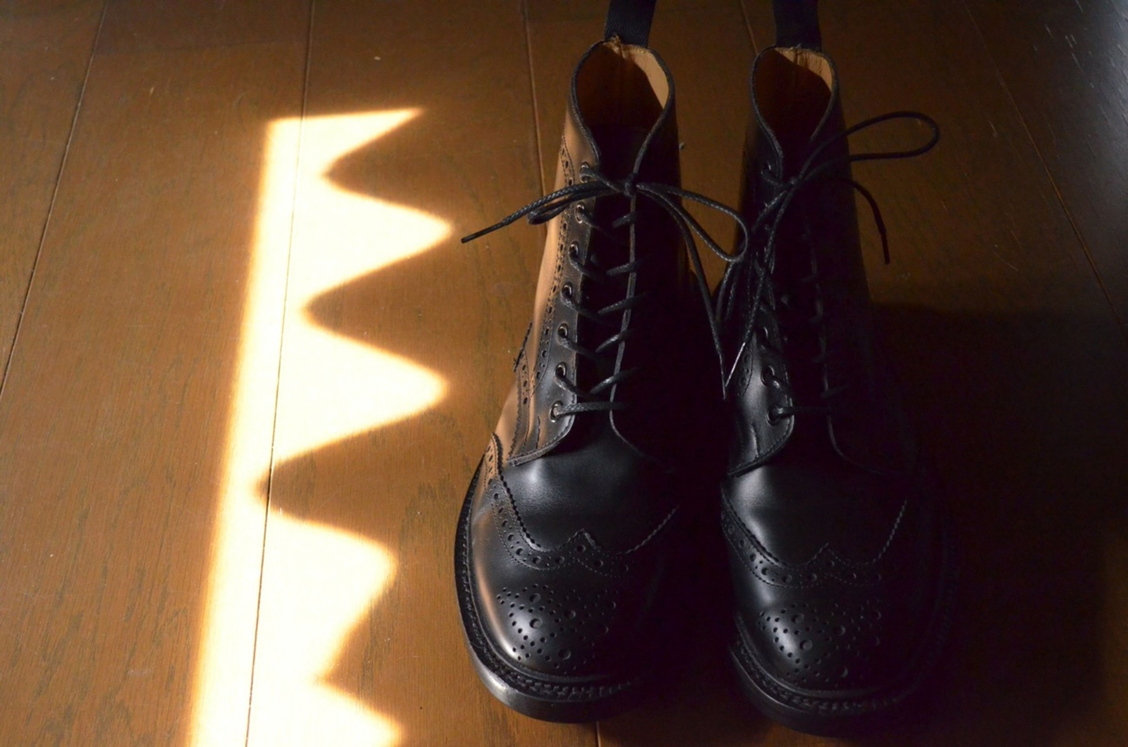 indoors, still life, wall - building feature, home interior, close-up, hanging, no people, high angle view, flooring, electricity, shoe, shadow, table, wall, floor, single object, technology, art and craft, black color, home
