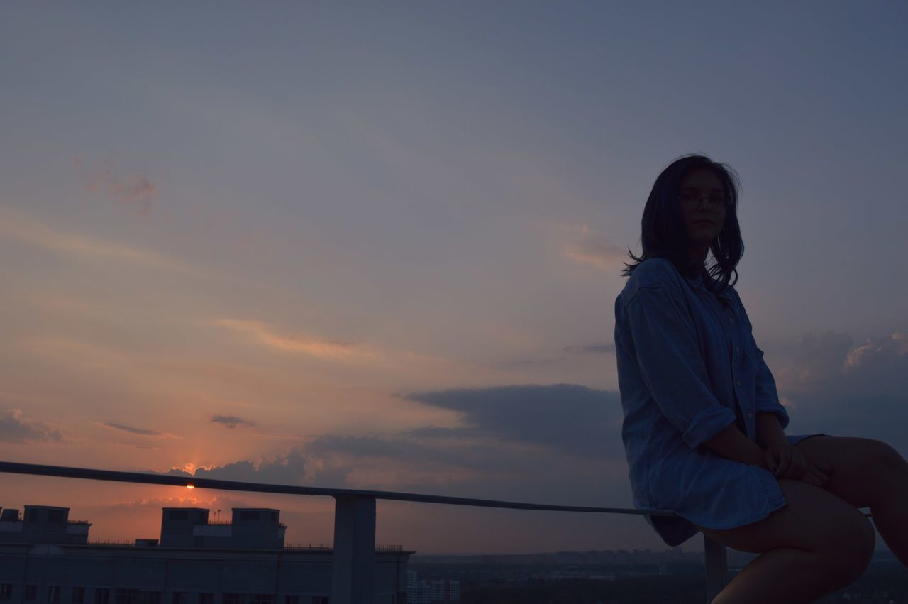 sunset, real people, sky, lifestyles, one person, leisure activity, connection, outdoors, standing, cloud - sky, architecture, built structure, women, nature, building exterior, city, young adult, day, people