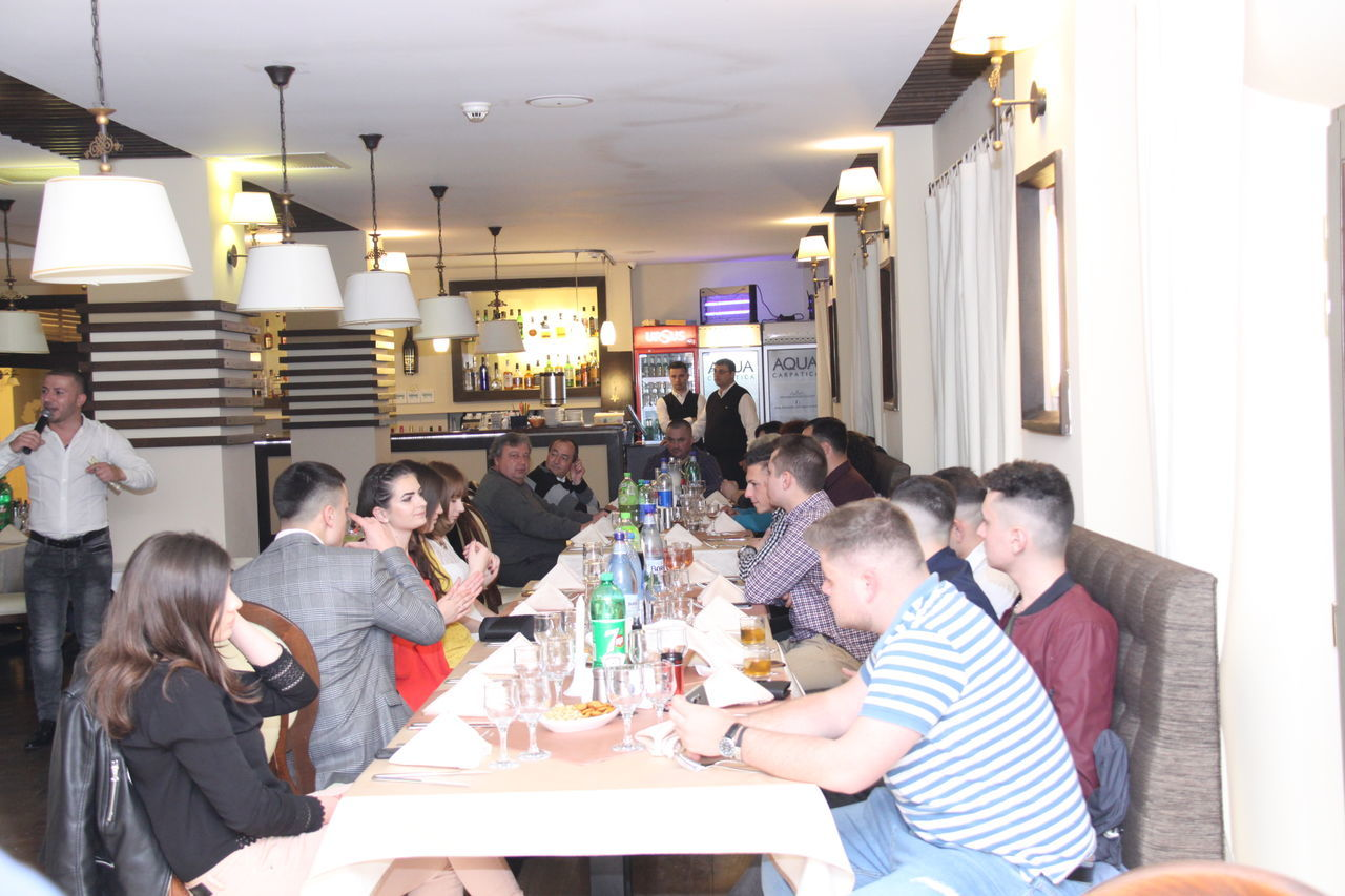 sitting, table, indoors, real people, medium group of people, illuminated, men, casual clothing, women, young men, togetherness, young adult, young women, technology, architecture, day, people