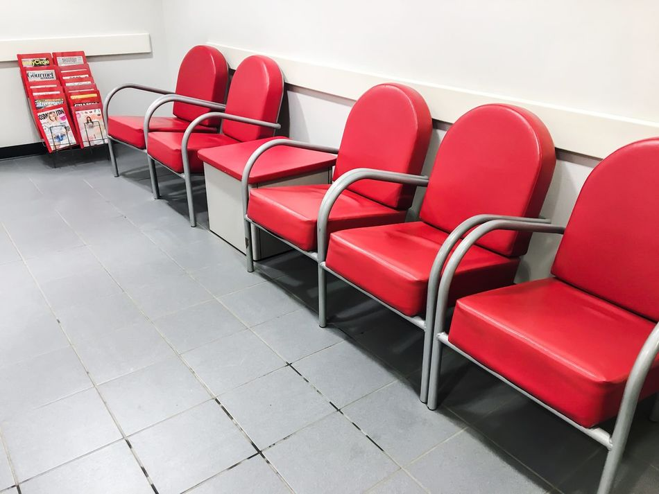 Chair Red Seat Empty High Angle View No People Armchair Indoors  Row Of Chairs Sterile Sterile Environment Waiting Room Waiting Magazine Stand Magazine Old Media Dentist Doctors Office Doctors Appointment  Appointment Red And White Bland Uncomfortable Boring Bored