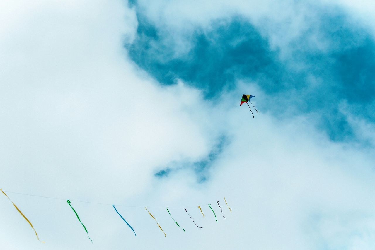 Low Angle View Of Kite Against Cloudy Sky