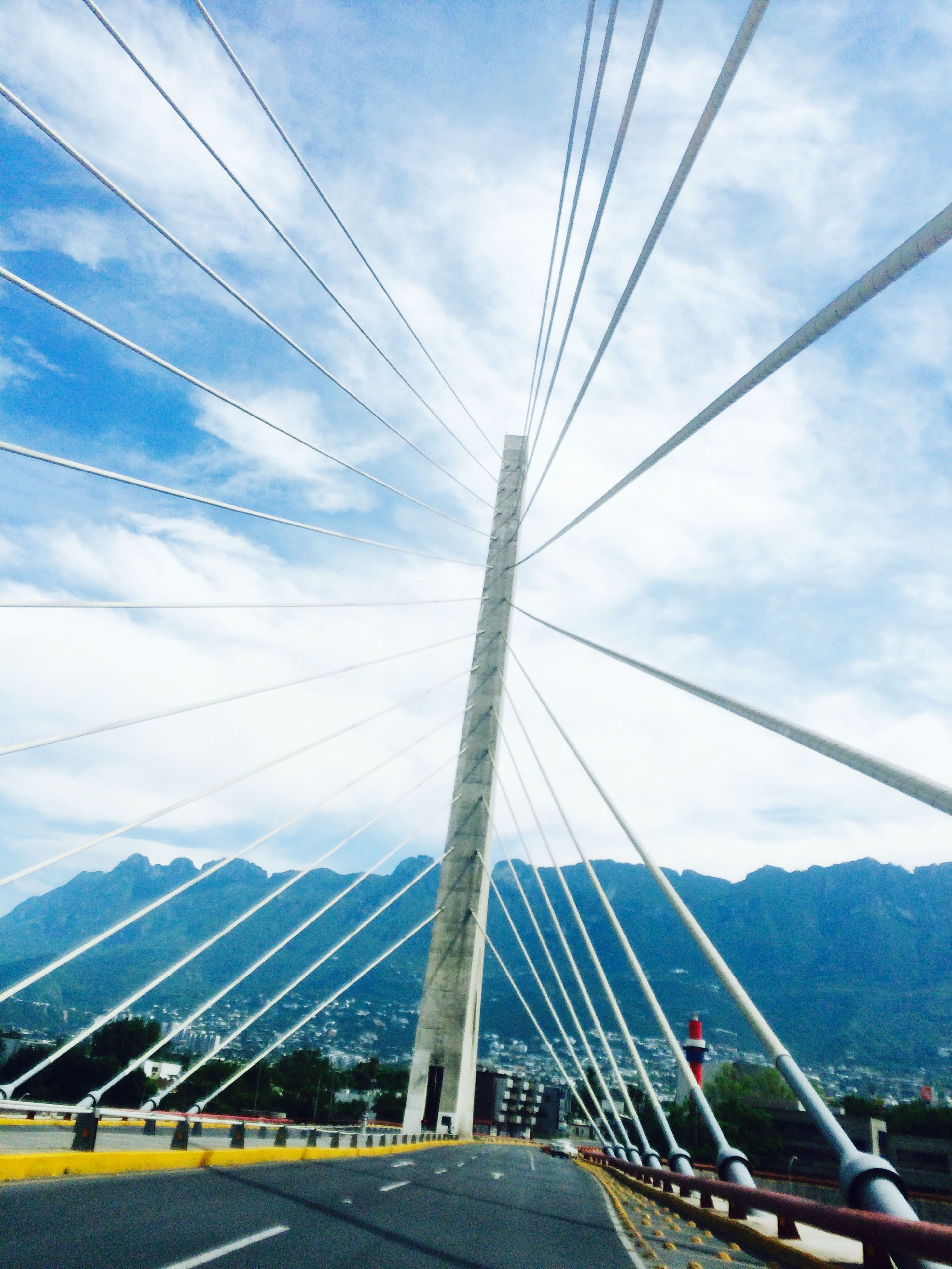 connection, transportation, sky, cable, power line, electricity pylon, bridge - man made structure, cloud - sky, built structure, road, engineering, architecture, suspension bridge, the way forward, cloud, blue, power supply, electricity, low angle view, cable-stayed bridge