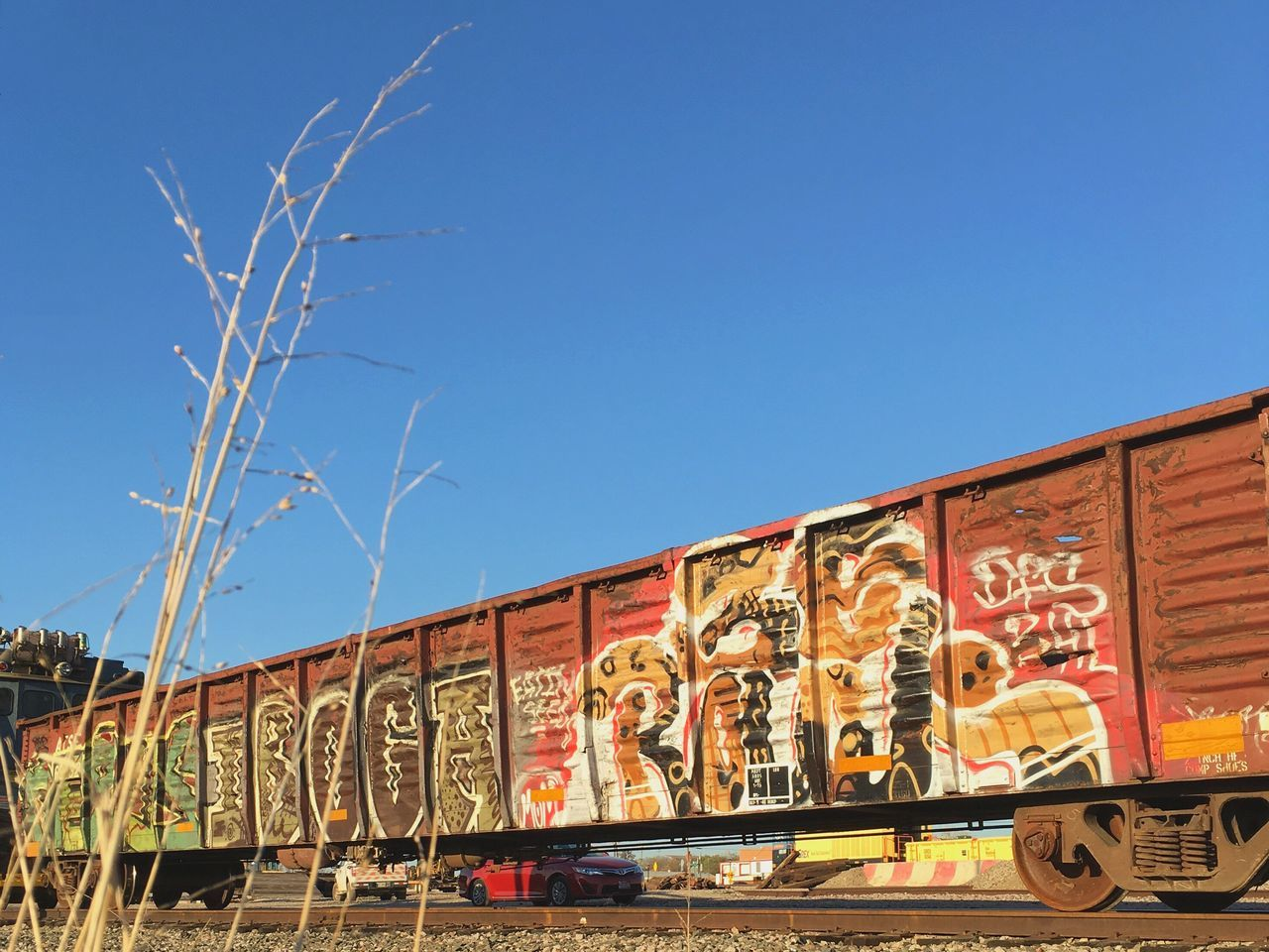 graffiti, text, blue, day, outdoors, architecture, built structure, transportation, clear sky, sunlight, no people, sky, city