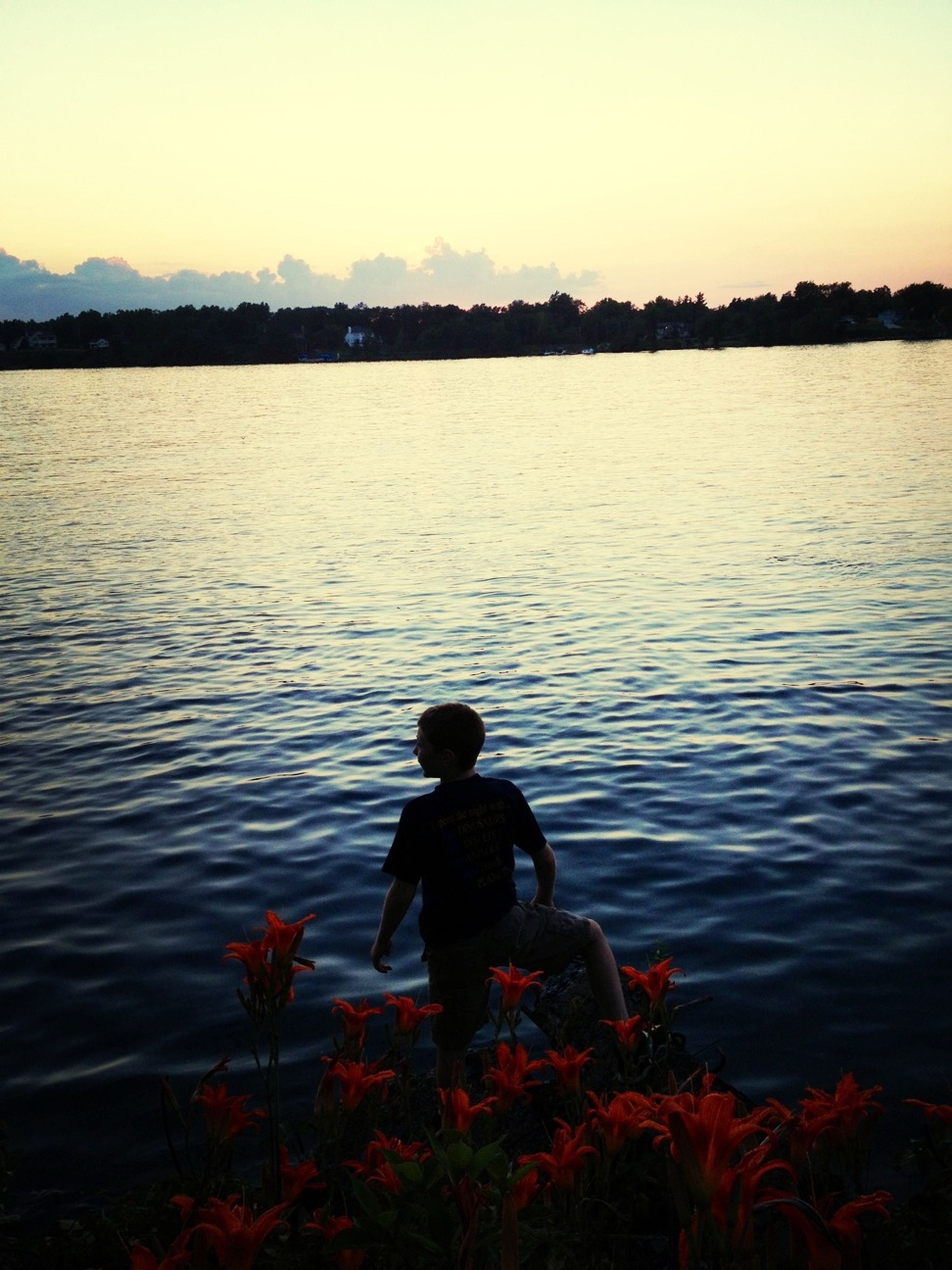 water, sunset, rear view, lake, lifestyles, tranquil scene, leisure activity, beauty in nature, scenics, tranquility, men, standing, nature, clear sky, silhouette, orange color, rippled, idyllic
