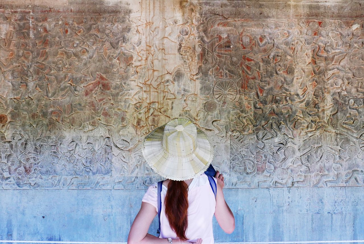 Angkor Wat walls always impress people. The Tourist The Tourist Mission Tourism Hat Girl Tourist Landmark Rocks Wall Sculpture Look Back No Face Voyage Outdoors Women ASIA The Week On EyeEm Market Bestsellers June 2016 Bestsellers
