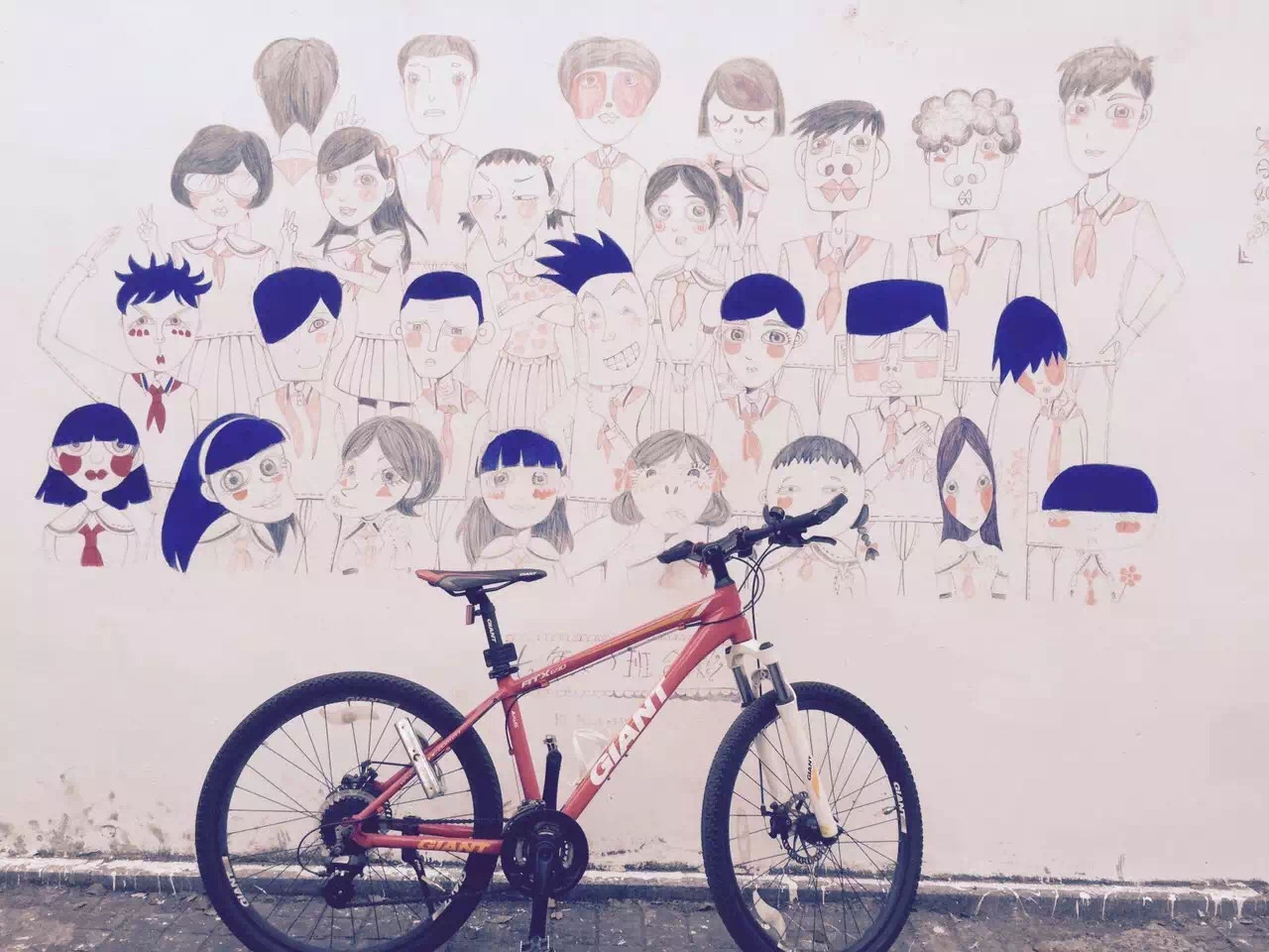 bicycle, transportation, land vehicle, mode of transport, stationary, parked, parking, wall - building feature, wheel, wall, cycle, leaning, day, graffiti, outdoors, no people, cart, street, built structure, text