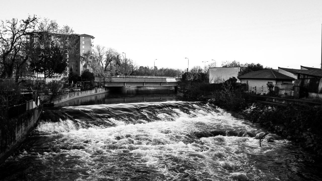 water, motion, flowing water, architecture, built structure, outdoors, hydroelectric power, long exposure, tree, fuel and power generation, nature, building exterior, day, no people, dam, waterfall, clear sky, watermill, power in nature, sky