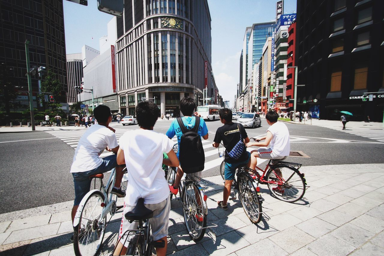 Rear View Of Boys With Bicycles On Footpath In City