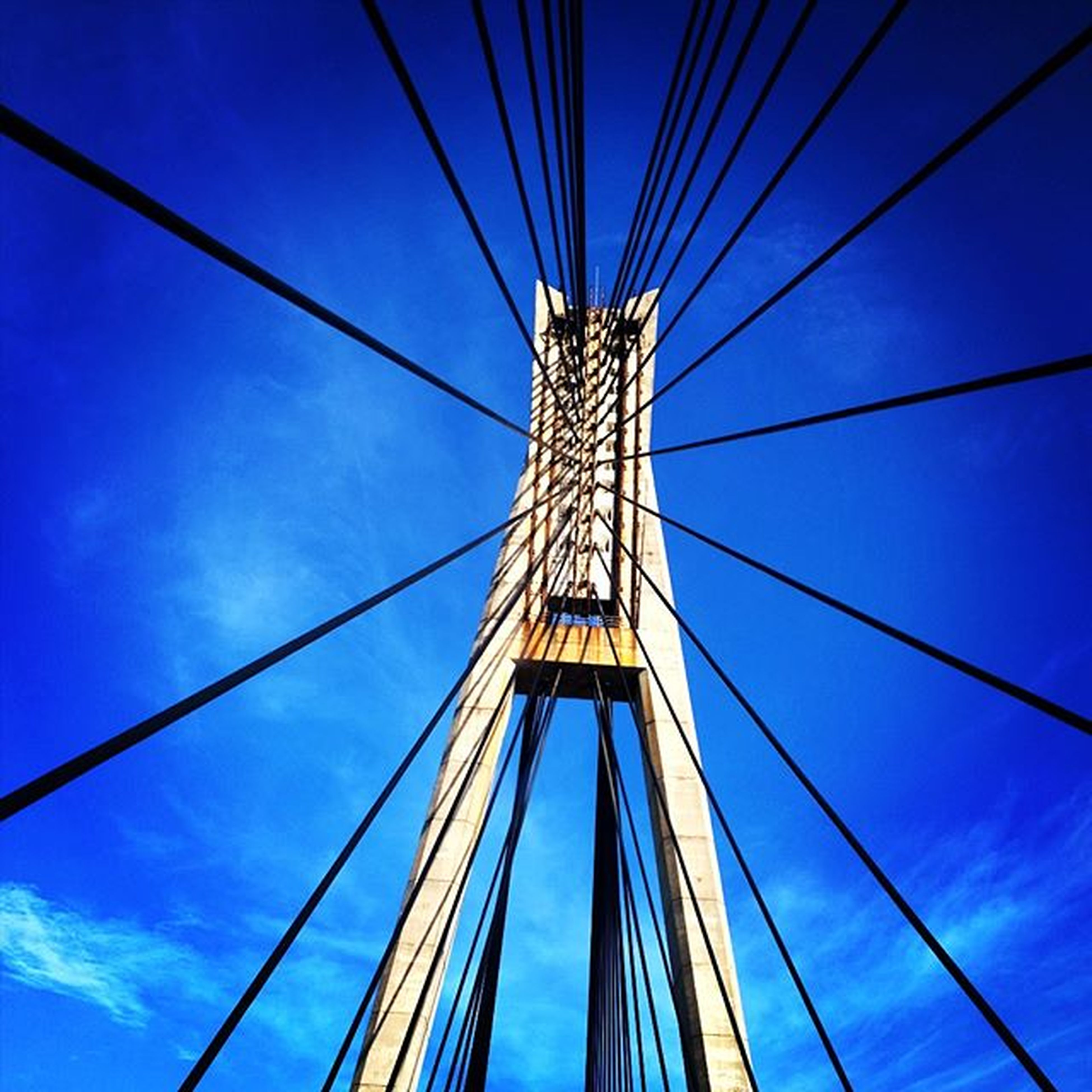 low angle view, blue, connection, cable, sky, built structure, suspension bridge, engineering, steel cable, power line, bridge - man made structure, electricity, cable-stayed bridge, transportation, architecture, electricity pylon, metal, day, part of, power supply
