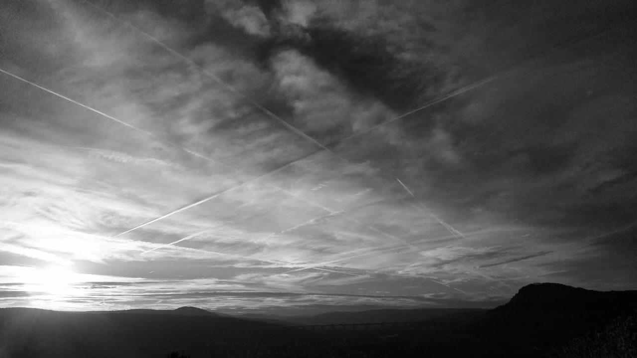 Low Angle View Of Vapor Trails In Cloudy Sky