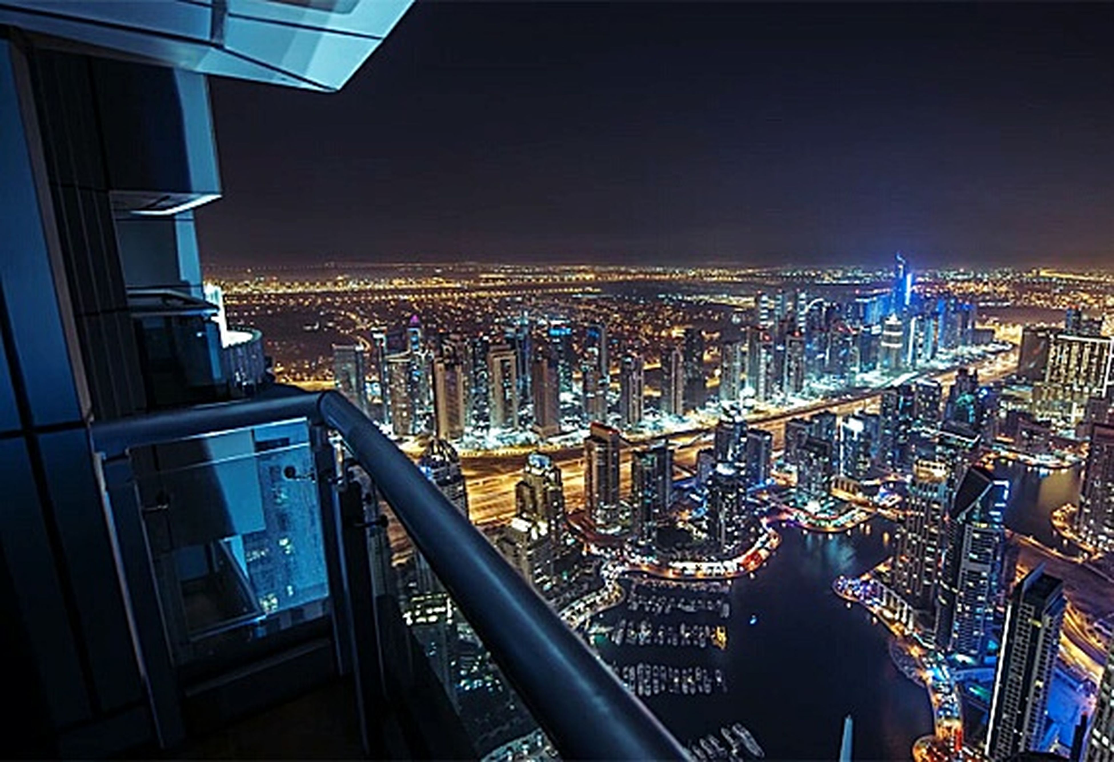 illuminated, architecture, built structure, cityscape, city, building exterior, night, modern, clear sky, sky, development, blue, dark, city life, capital cities, office building, horizon, no people, human settlement, horizon over land, flying, financial district, residential district