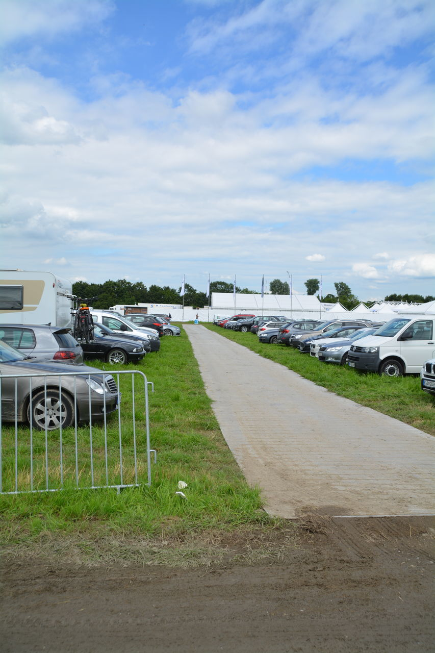 Footpath Amidst Cars Parked On Field Against Sky