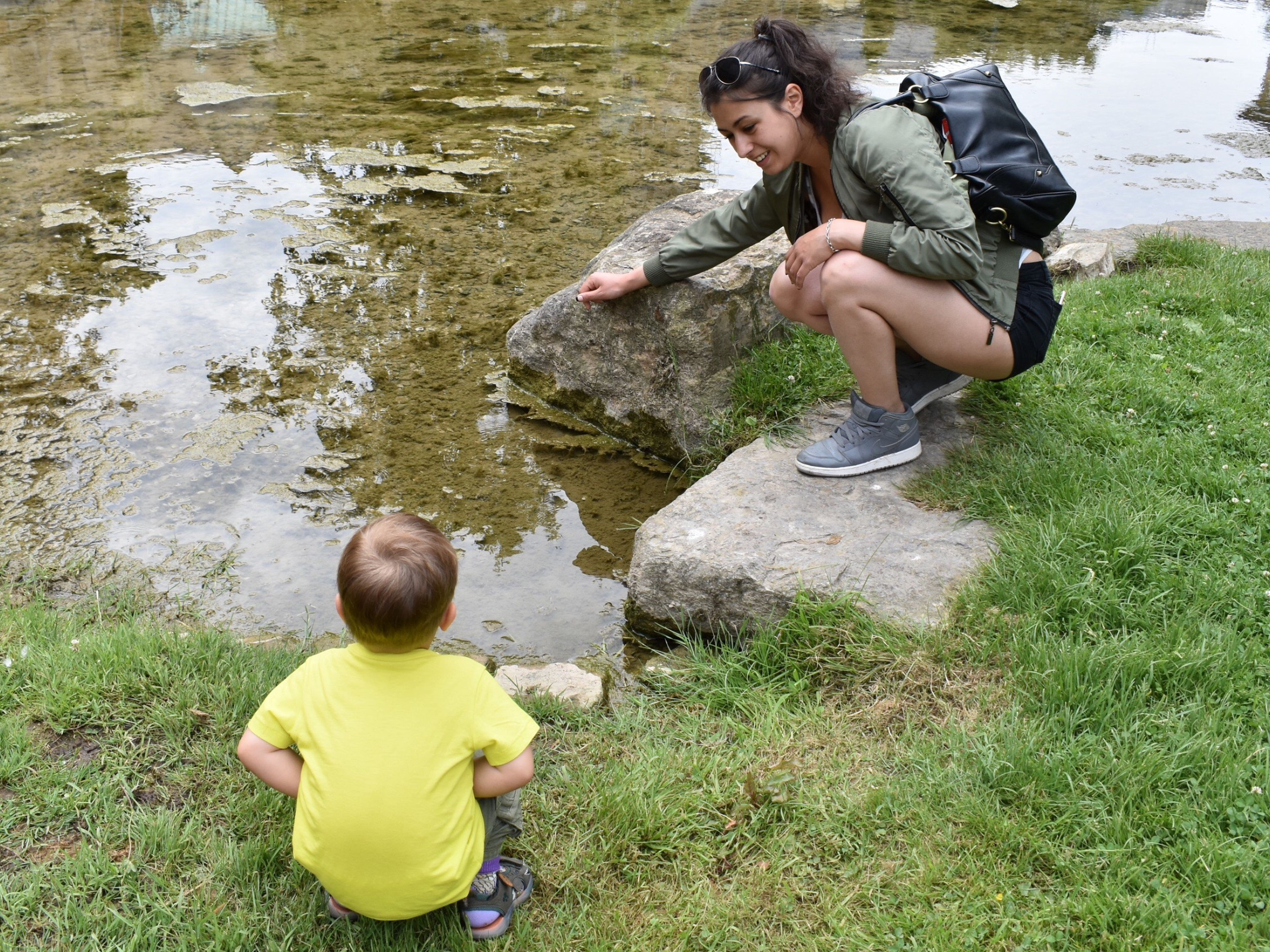 childhood, two people, real people, water, casual clothing, day, rock - object, full length, outdoors, boys, lake, leisure activity, togetherness, crouching, nature, grass, animal themes, people, adult