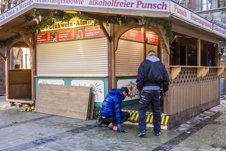 Dismantling market stall at Munich Christmas market in Marienplatz, Germany. Christmas Market Dismantling Architecture Building Exterior Built Structure End Full Length Lifestyles Men Outdoors People Real People Season  Stall Standing Two People Working Workmen