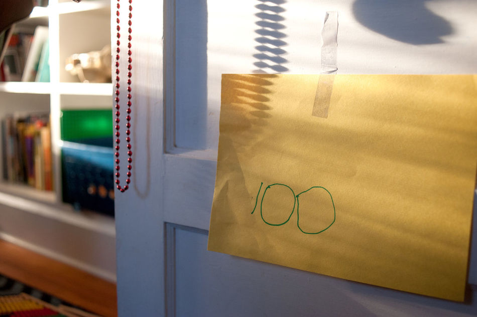 """The number """"100 written in child's handwriting on a piece of yellow construction paper for """"100 day"""" taped to a door. 100 100 Days 100 Followers Alone Art Color Copy Space D Drawing Kid Light Nuartapp Paper"""