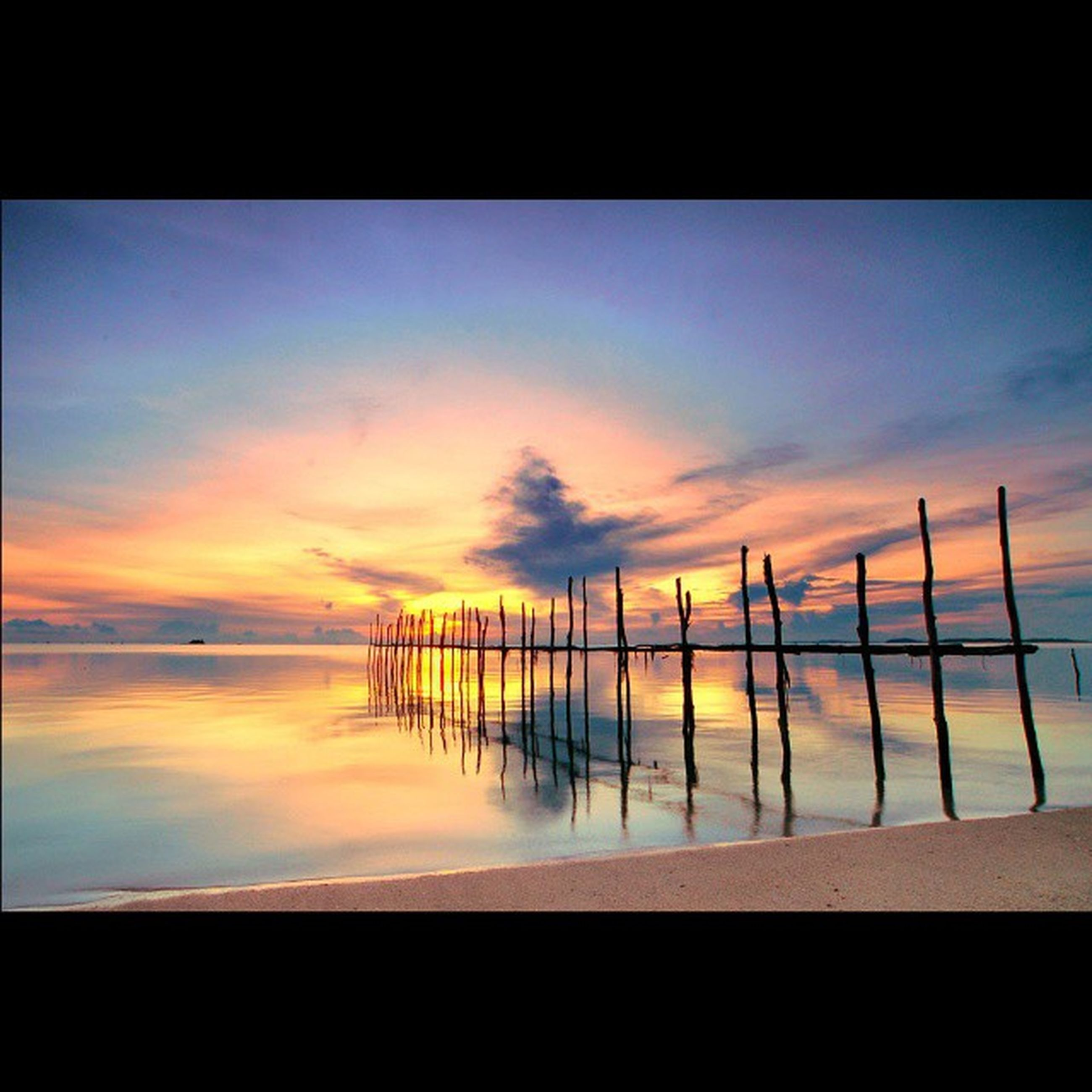 sea, sunset, water, sky, tranquil scene, tranquility, beach, scenics, horizon over water, beauty in nature, nature, shore, cloud - sky, idyllic, silhouette, pier, cloud, wooden post, reflection, orange color