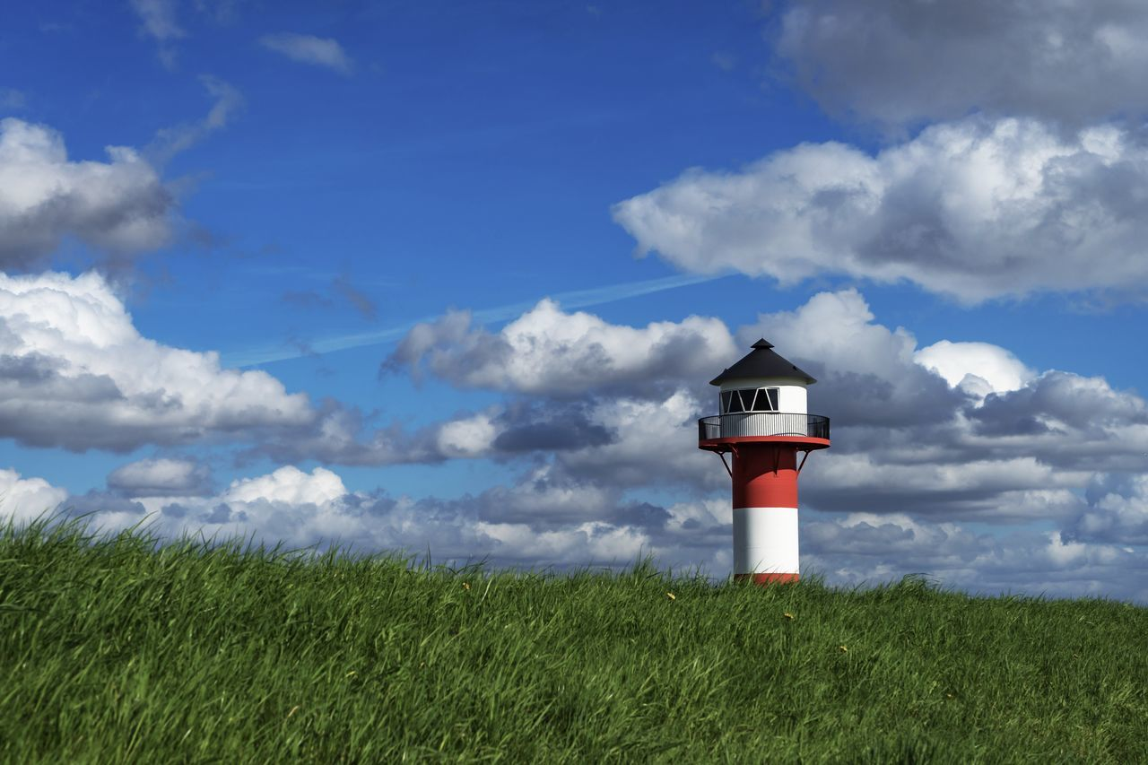 lighthouse, cloud - sky, safety, guidance, grass, sky, protection, security, architecture, direction, growth, building exterior, day, tower, field, green color, built structure, no people, nature, outdoors, scenics, landscape, lookout tower, beauty in nature