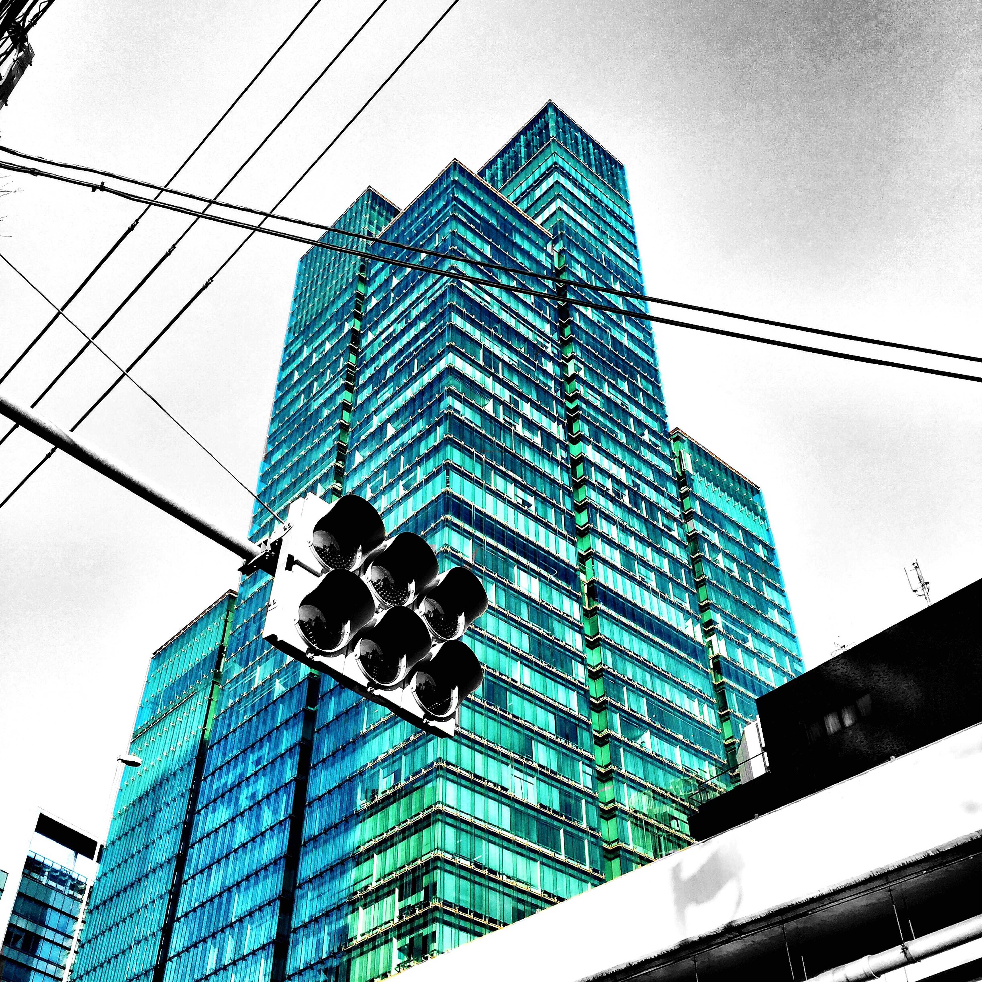 building exterior, architecture, low angle view, built structure, office building, modern, city, skyscraper, tall - high, tower, building, clear sky, sky, blue, reflection, glass - material, day, outdoors, no people, city life