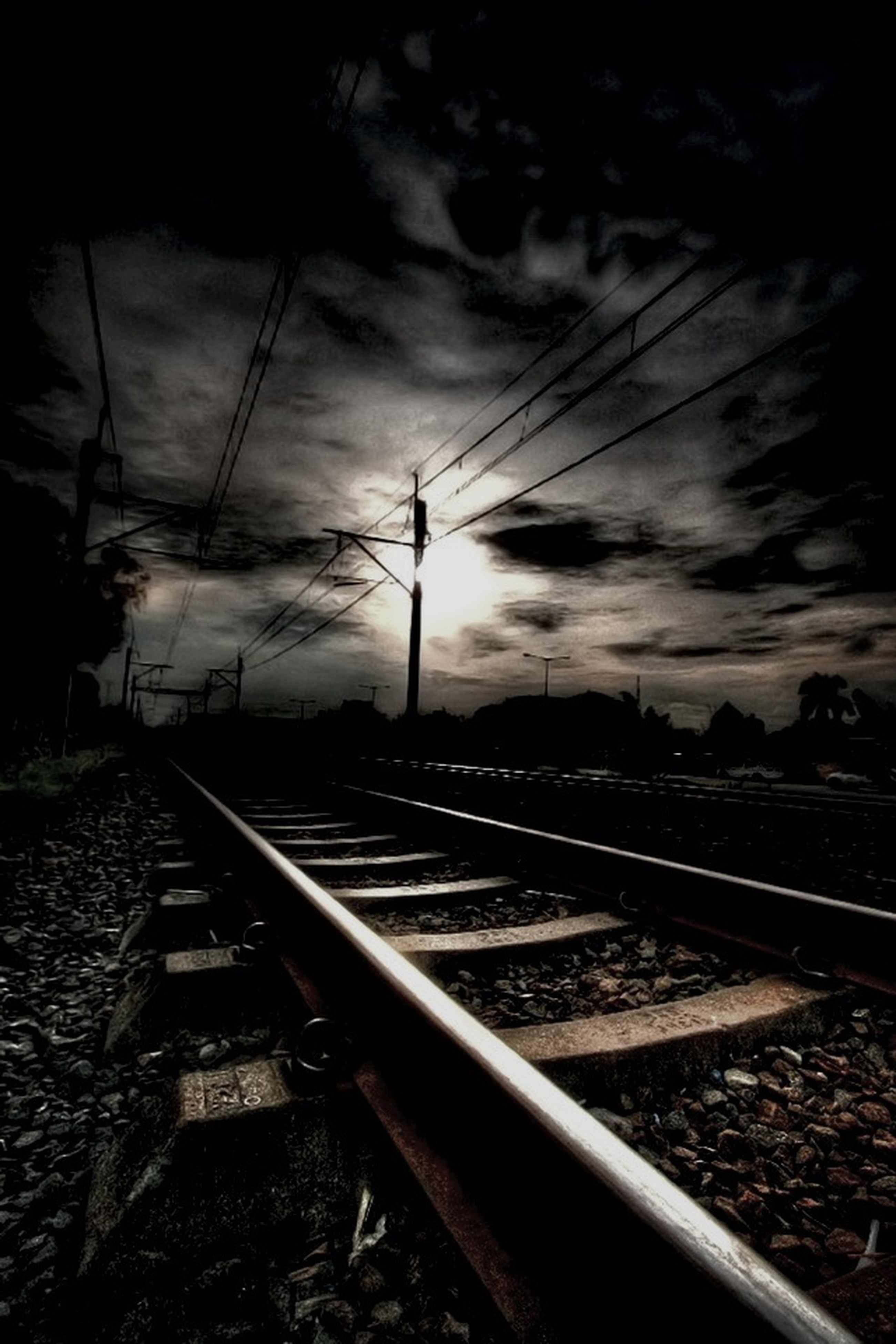 railroad track, rail transportation, sky, cloud - sky, power line, transportation, electricity pylon, public transportation, cloudy, sunset, railroad station platform, railroad station, cloud, electricity, cable, connection, railway track, power supply, diminishing perspective, outdoors
