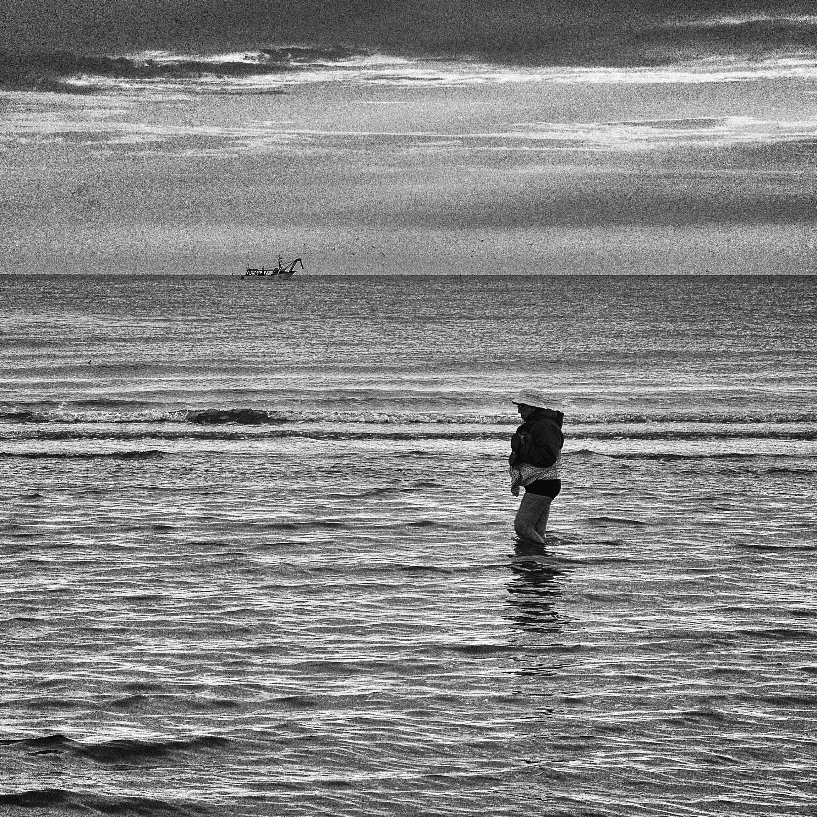 sea, water, horizon over water, lifestyles, beach, leisure activity, tranquility, sky, tranquil scene, rear view, shore, men, scenics, silhouette, standing, beauty in nature, full length, nature