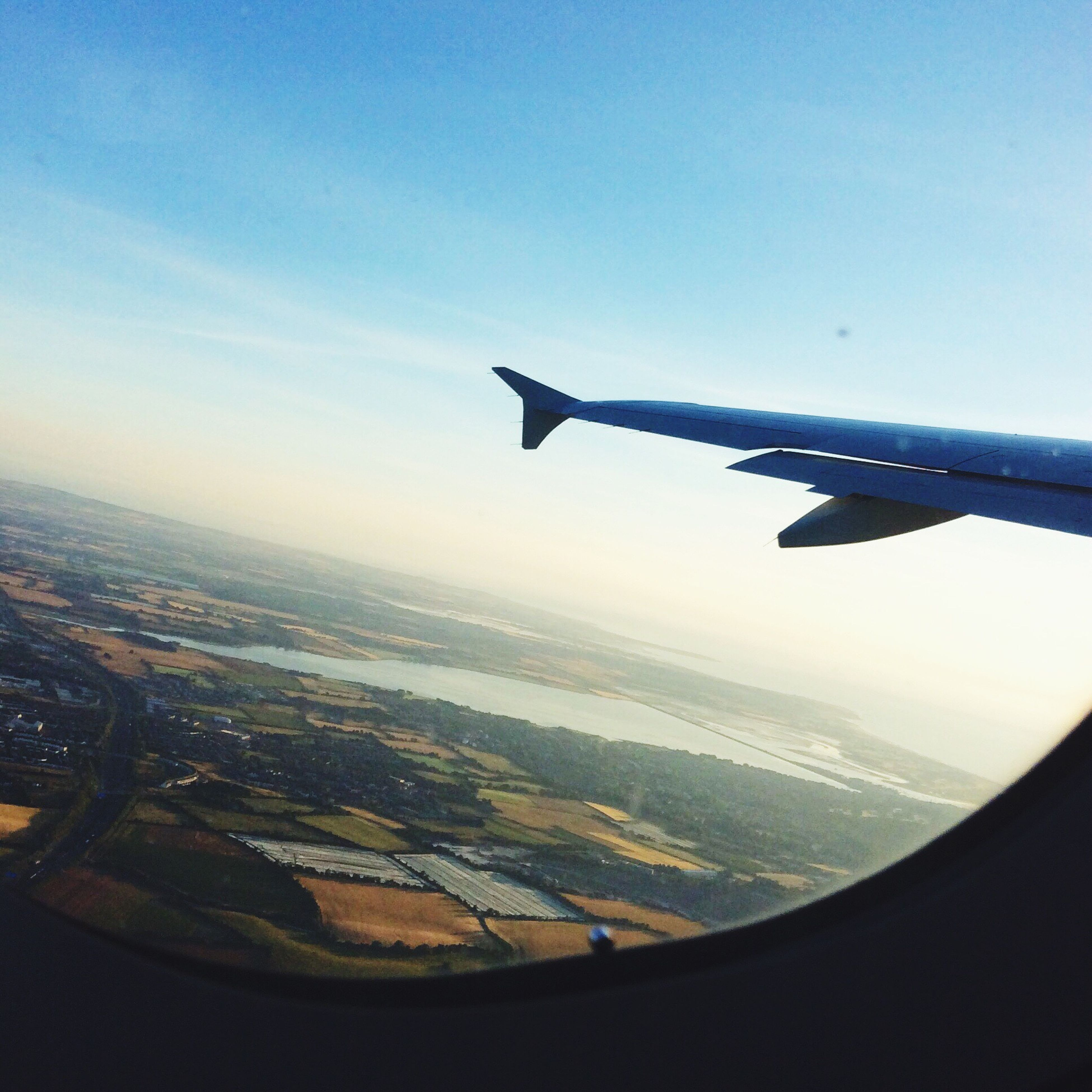 airplane, aircraft wing, air vehicle, part of, cropped, transportation, mode of transport, flying, aerial view, landscape, travel, journey, on the move, sky, mid-air, water, scenics, sea, cloud, aeroplane, blue, cloud - sky, airplane wing, beauty in nature, idyllic, horizon, nature, tranquility, day, cityscape, tranquil scene, majestic, coastline, outdoors