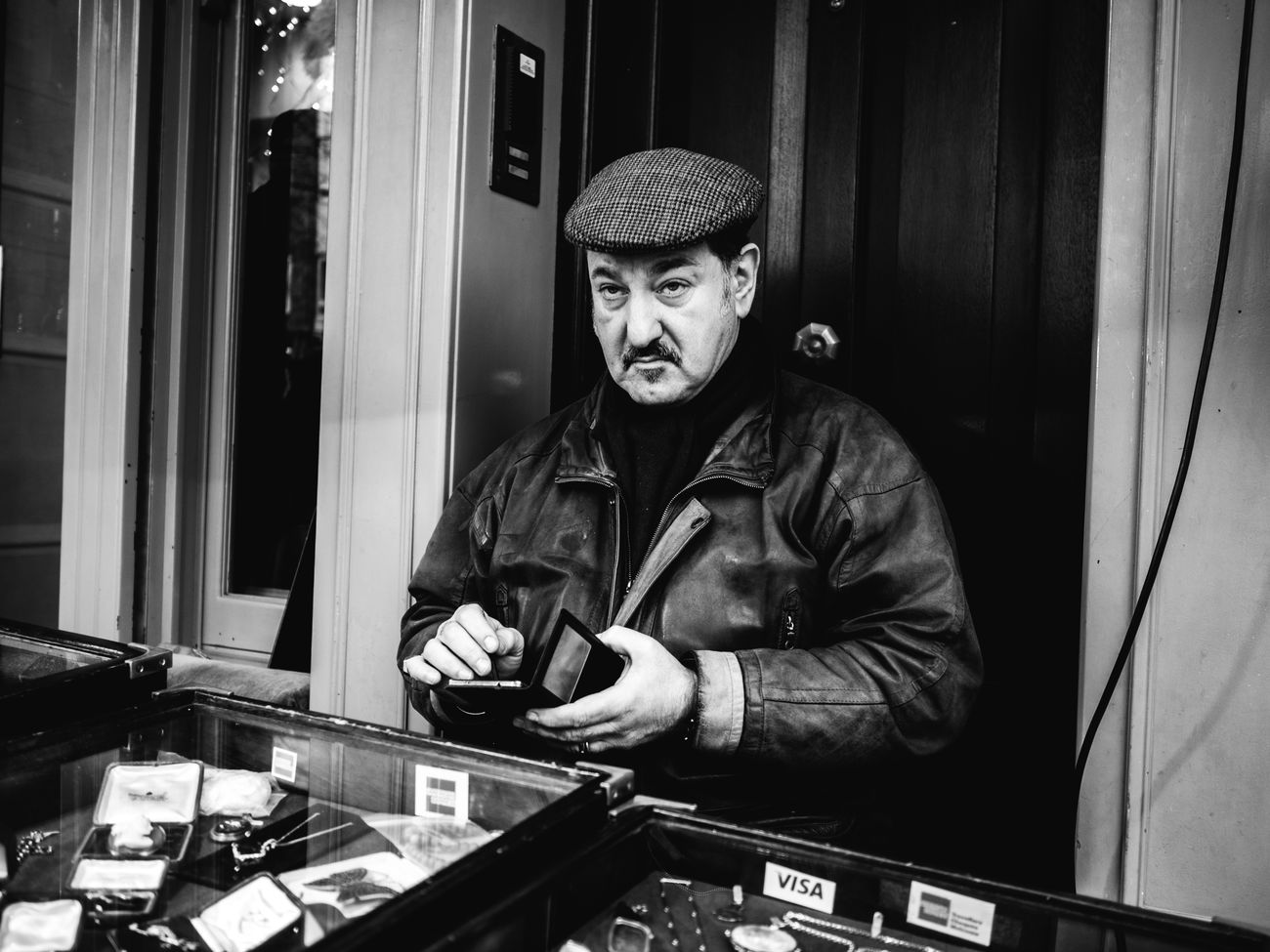 Street Trader. Streetlife Maxgor.com Candid Lifestyles Cıty Rawstreets 35mm Monochrome Photography Prime Lens London City Life Stranger Street Photography Olympus Pen F Black And White Photography Street Portrait Portrait Trader Market Market Trader Notting Hill Portobello Market