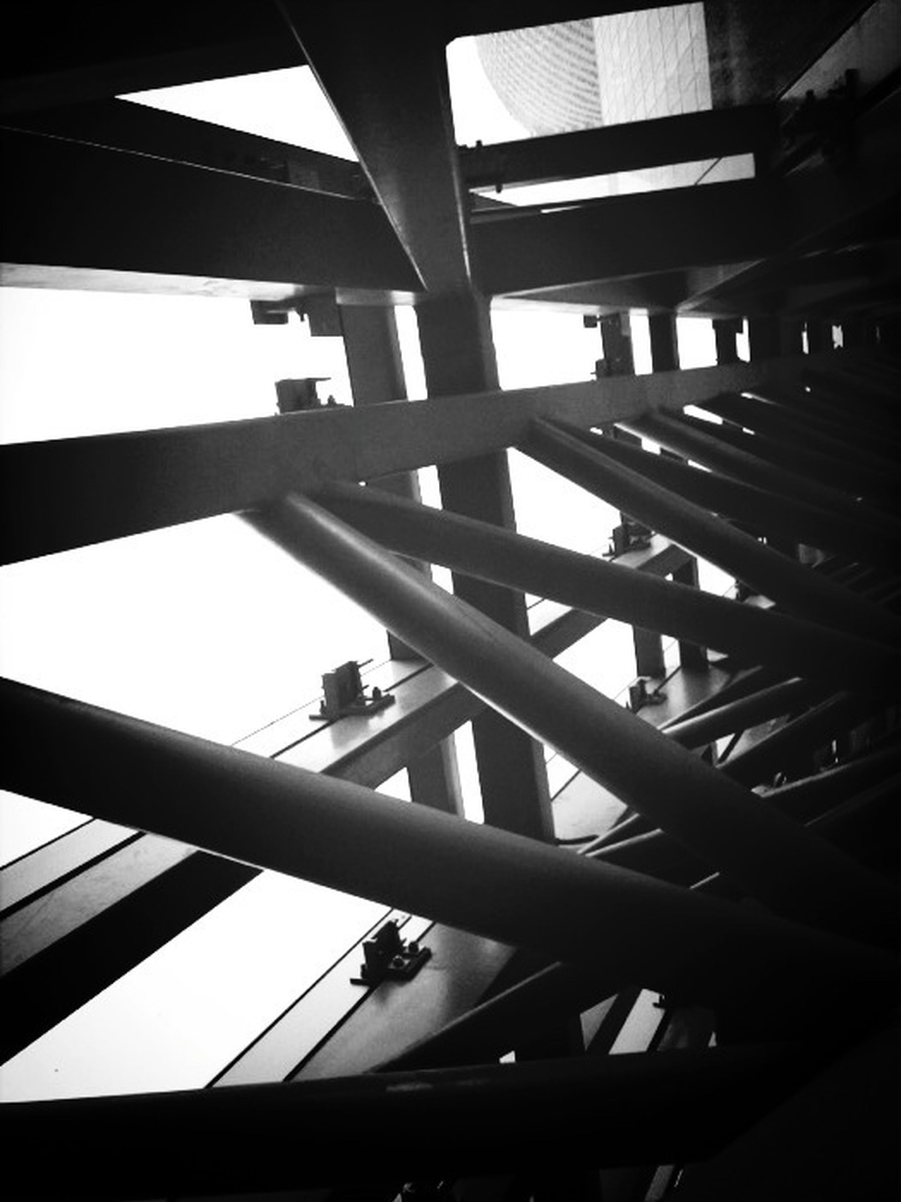 low angle view, built structure, architecture, indoors, metal, directly below, modern, pattern, ceiling, metallic, sky, no people, day, silhouette, geometric shape, architectural feature, railing, grid, sunlight, glass - material