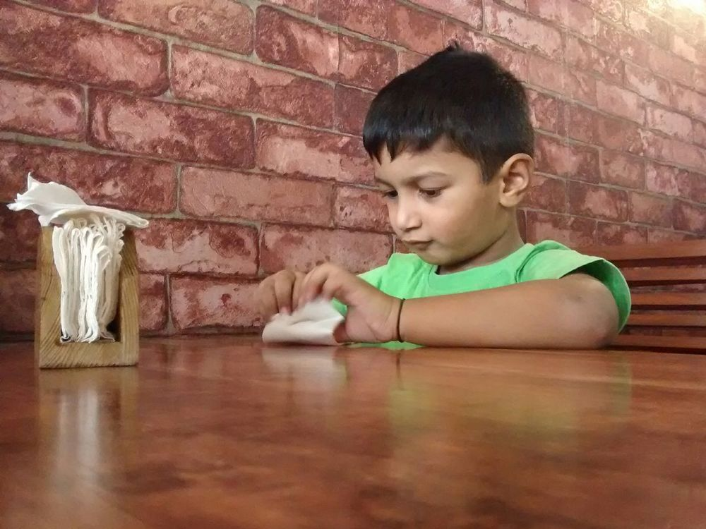 Kid playing with tissues Brick Wall Wall - Building Feature Waist UpBricks Casual Clothing Innocence Child Playing TissuePaper Tissue Box Restaurant Bric