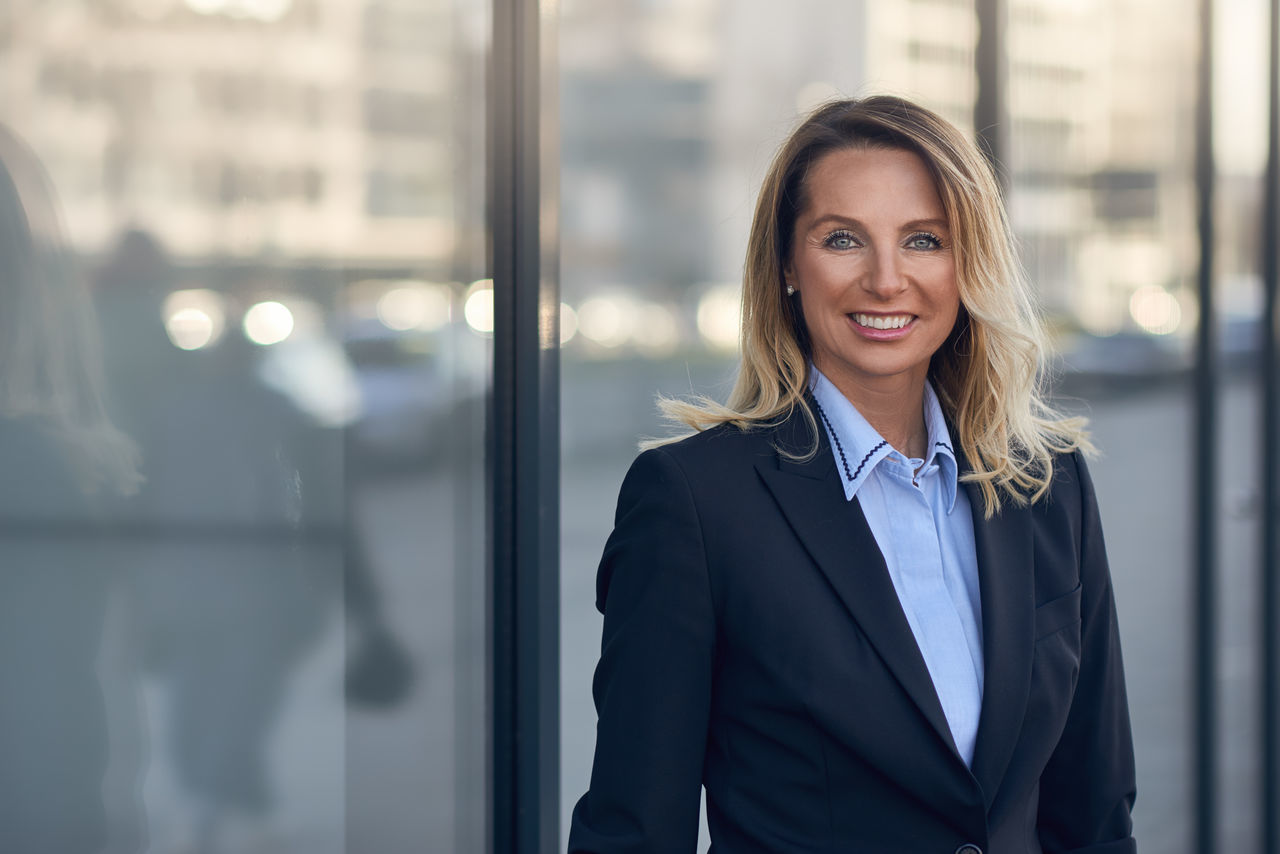 Smiling businesswoman in front of a glass window Blond Business Business Businesswoman Ceo Confidence  Executive  Female Happiness Mana Manager Mature Adult Middle-aged One Person Outdoors Portrait Smiling Successful Suit Well-dressed Woman