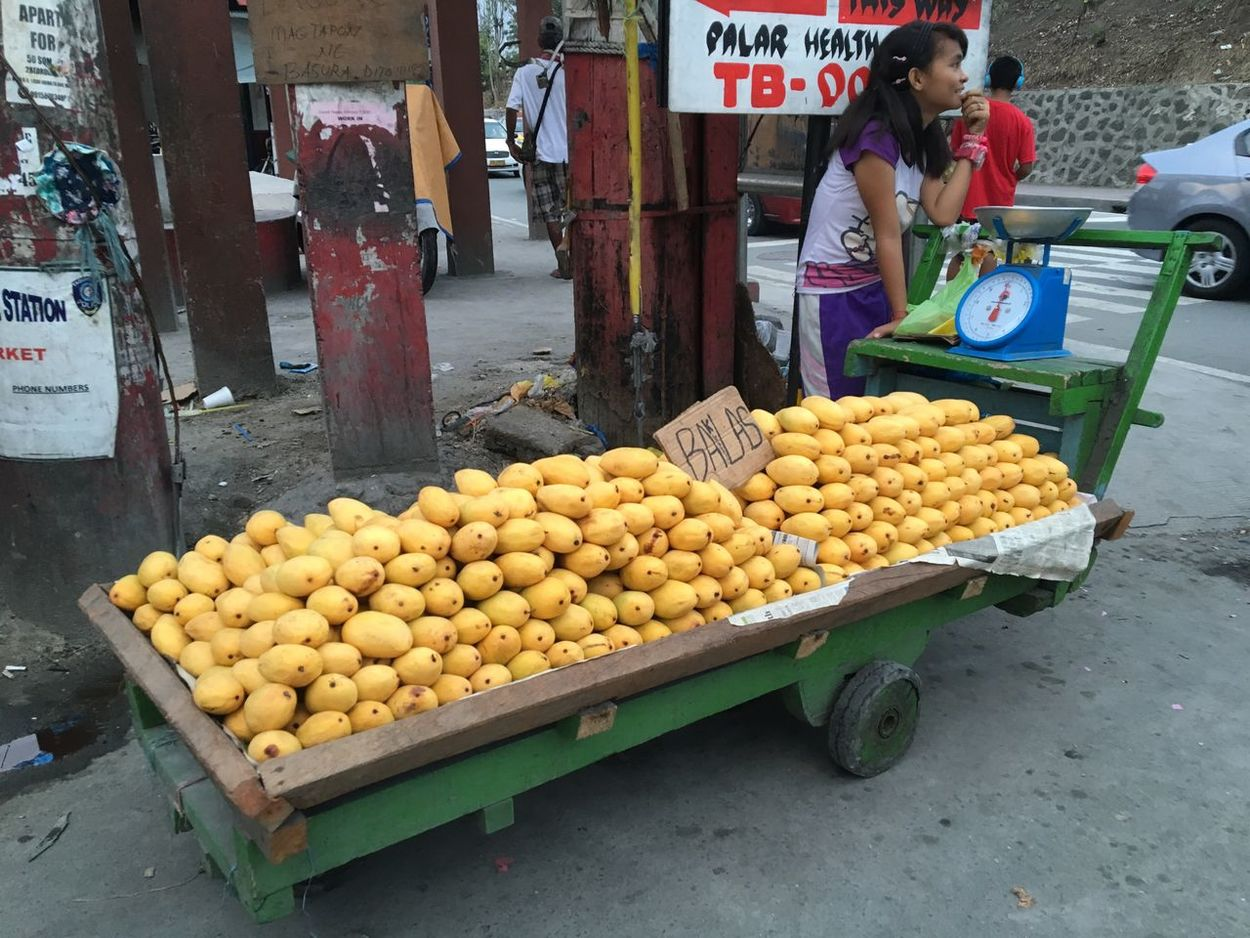 A girl selling mangoes waits for customers at her mobile pushcart shop at streetcorner in Palar, Makati City in the Philippines. Vendors The Shop Around The Corner Mangoes Ripe Mangoes Streetcorner