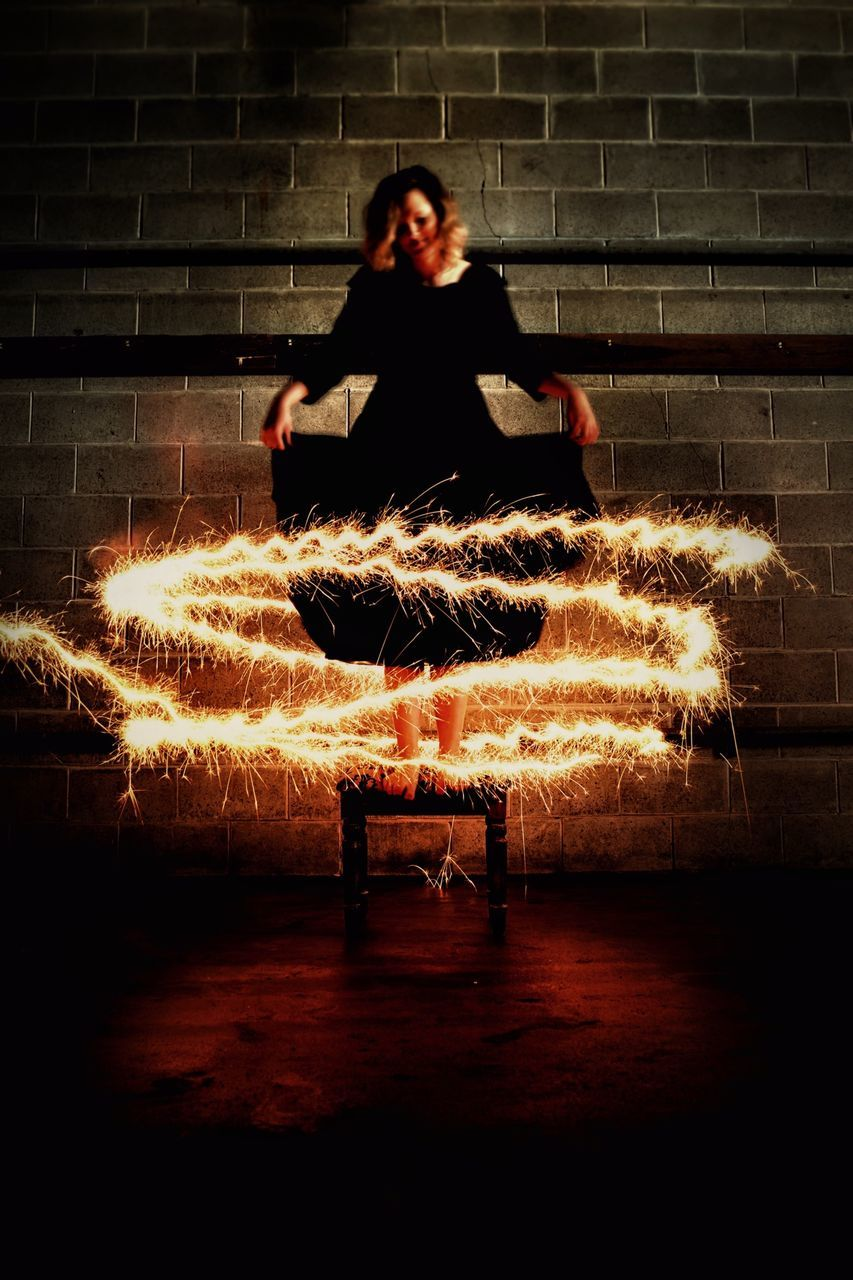 Front View Of Young Woman Holding Black Dress On Stool Surrounded By Sparkler Light Trail