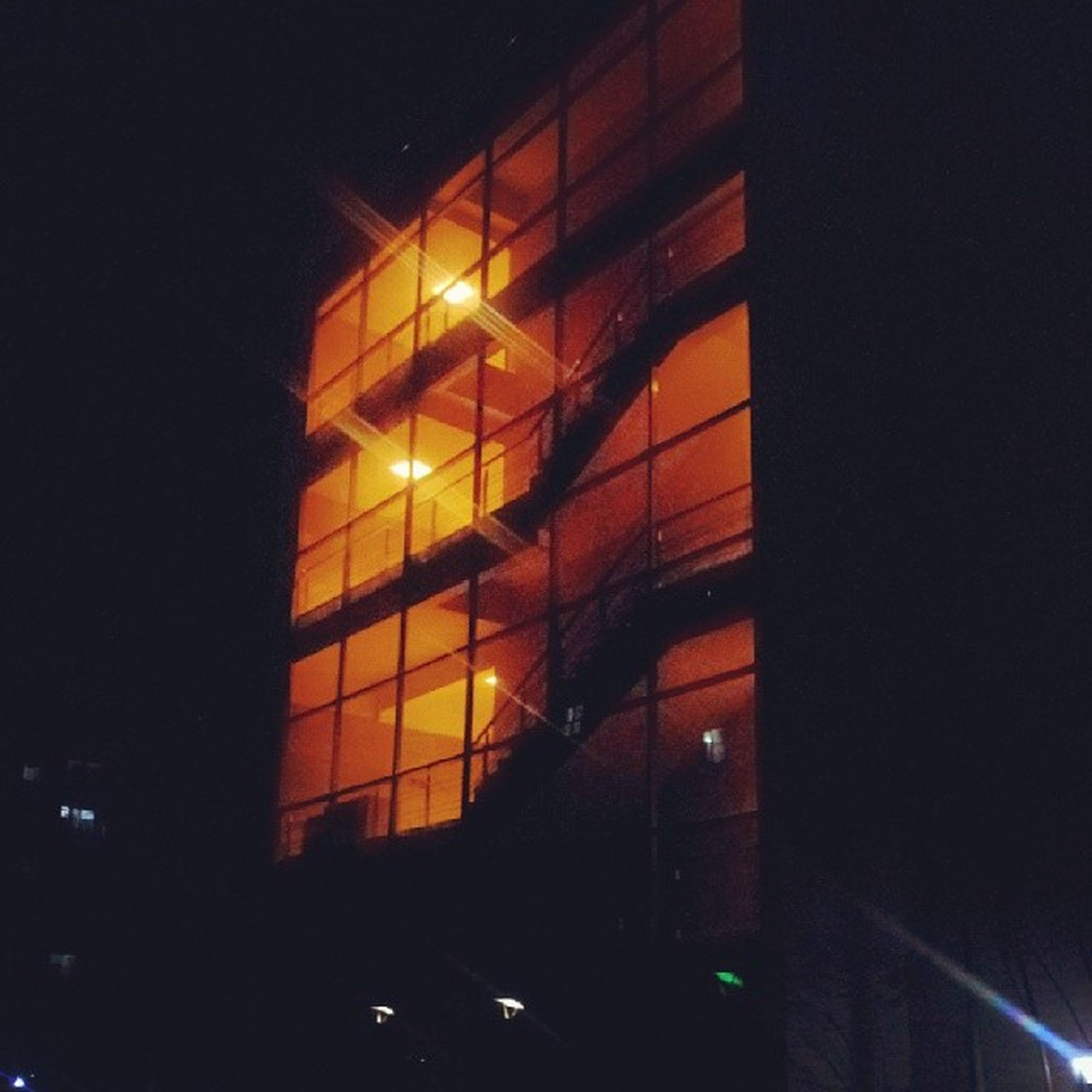 illuminated, night, window, dark, architecture, built structure, indoors, lighting equipment, glass - material, light - natural phenomenon, low angle view, building exterior, glowing, building, no people, silhouette, light, reflection, pattern, transparent